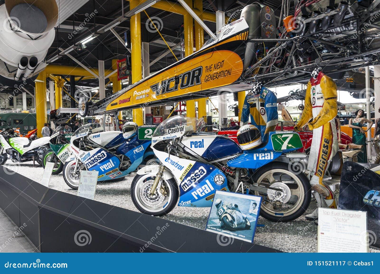 Συναγωνιμένος μοτοσικλέτες και αθλητικός εξοπλισμός στην επίδειξη στο αυτοκίνητο μουσείο