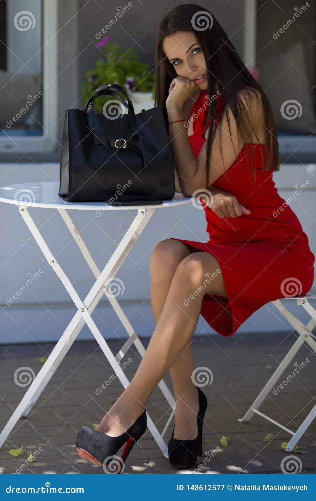 συνεδρίαση κοριτσιών στην καρέκλα στα κομψά παπούτσια με μια μοντέρνη μαύρη τσάντα