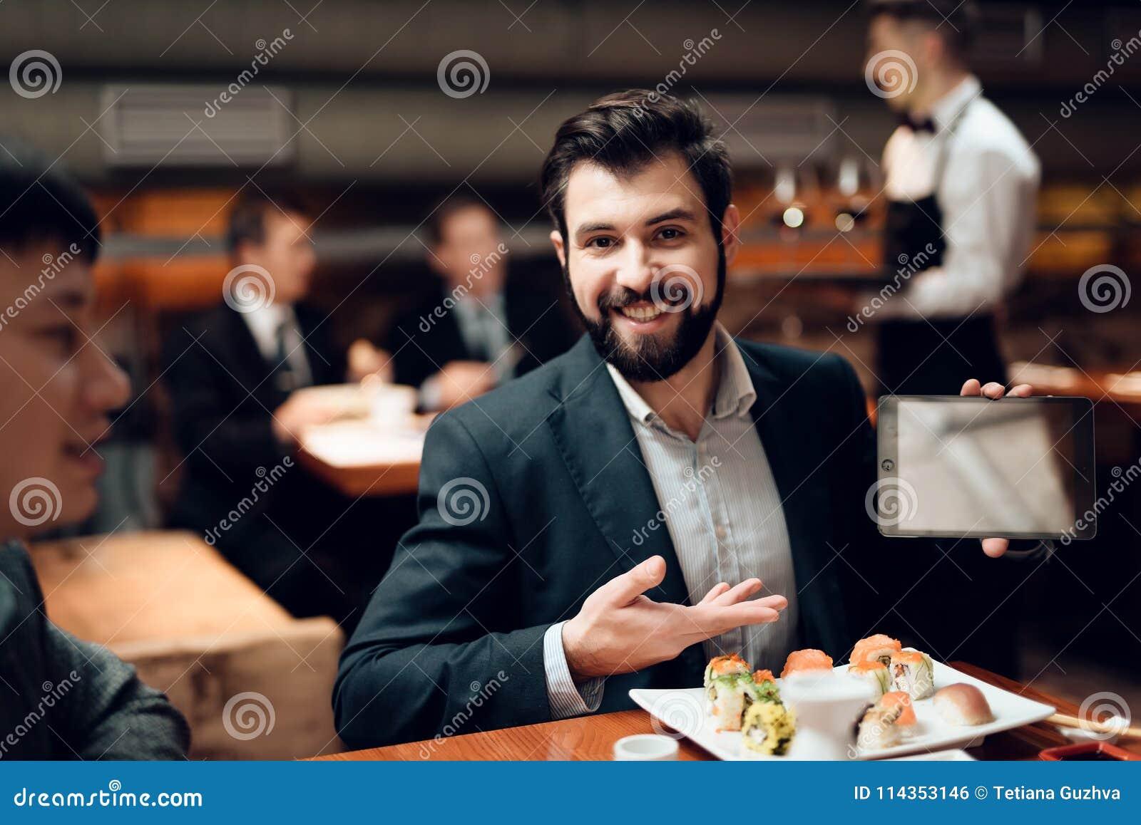 Συνεδρίαση με τους κινεζικούς επιχειρηματίες στο εστιατόριο Το άτομο παρουσιάζει ταμπλέτα