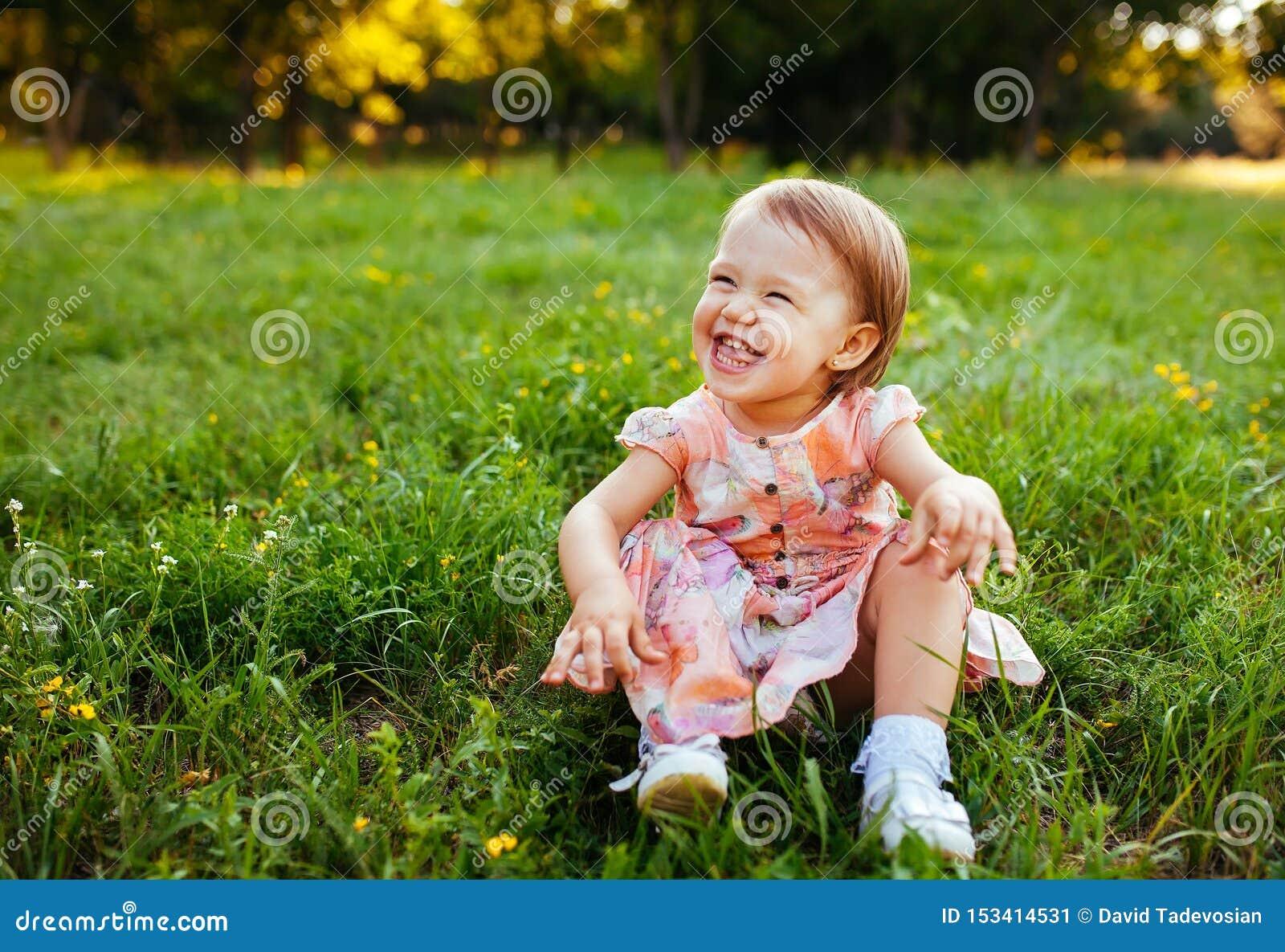 Συνεδρίαση μικρών κοριτσιών στη χλόη στο πάρκο