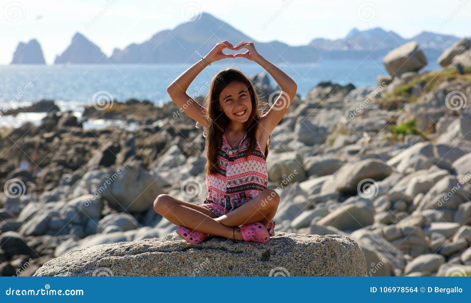 Συνεδρίαση μικρών κοριτσιών στους βράχους στο ωκεάνιο μέτωπο στη θάλασσα απότομων βράχων θερέτρου Los Cabos Μεξικό