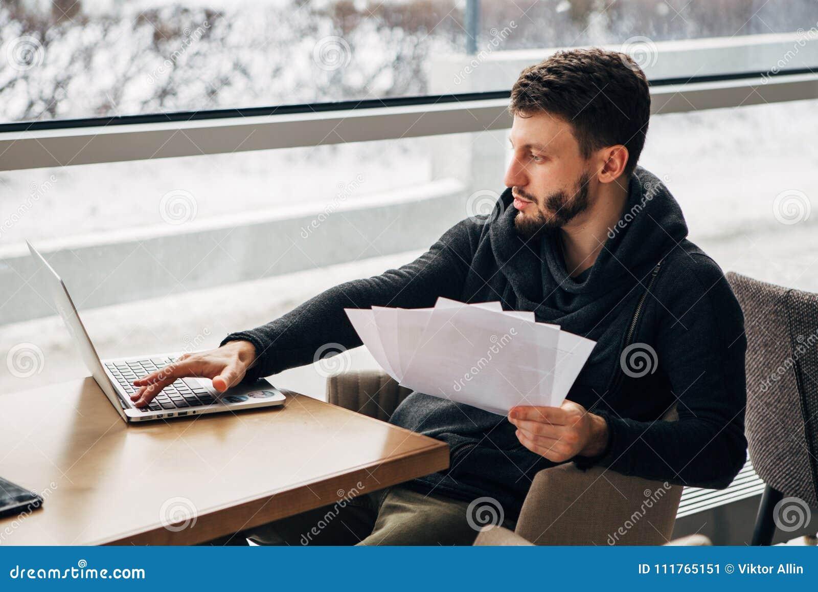 Συνεδρίαση νεαρών άνδρων στον καφέ και χρησιμοποίηση του lap-top