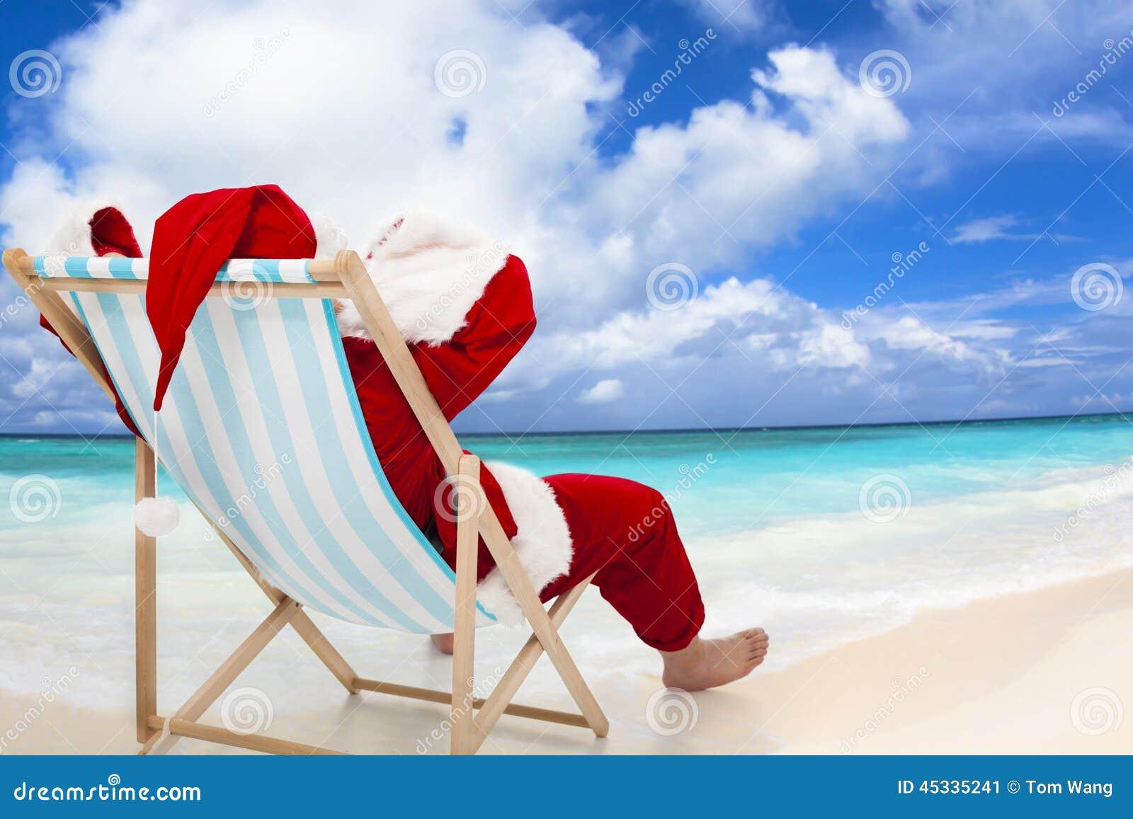 Συνεδρίαση Άγιου Βασίλη στις καρέκλες παραλιών Έννοια διακοπών Χριστουγέννων