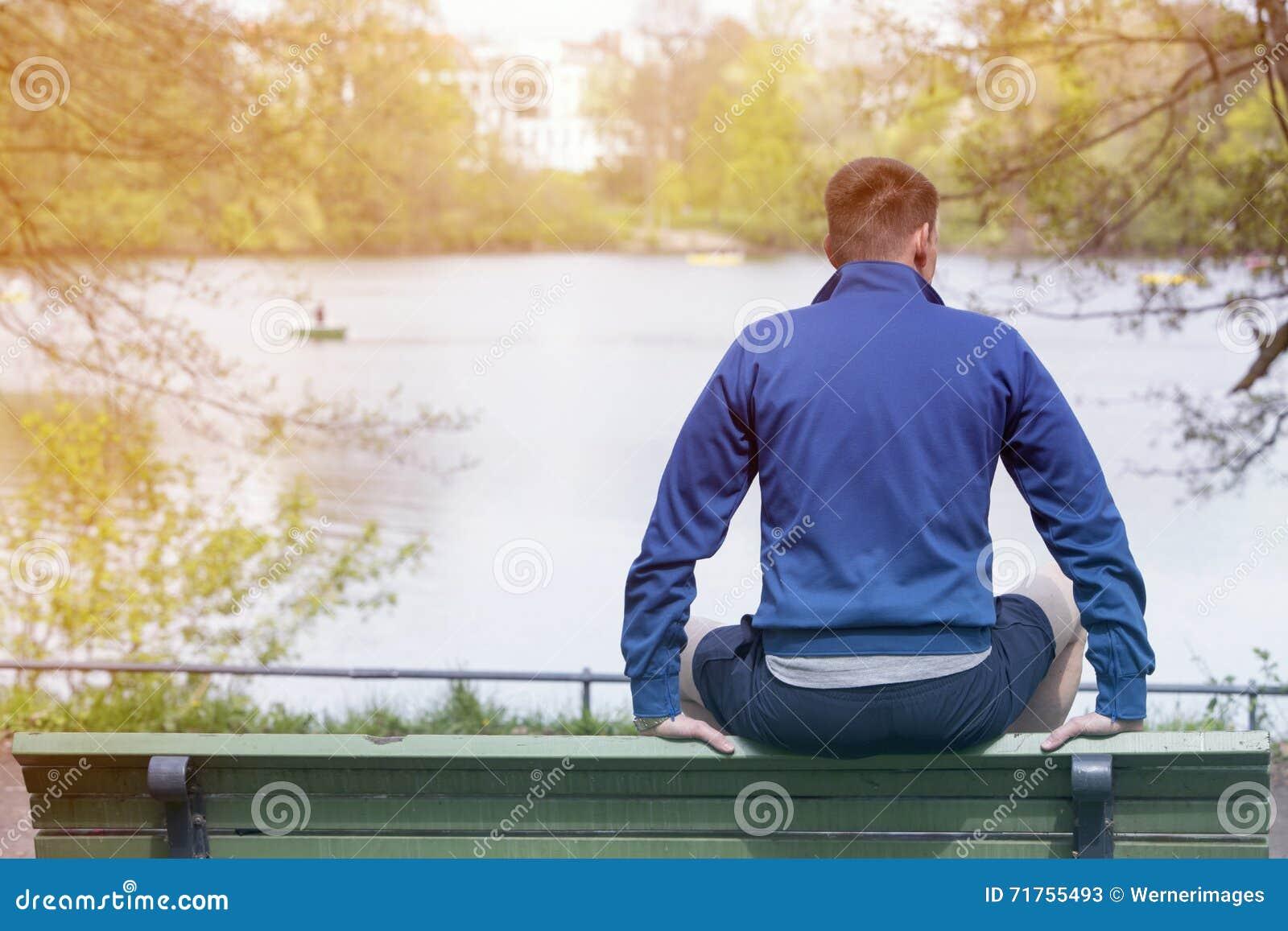 Συνεδρίαση ατόμων στον πάγκο και εξέταση μια λίμνη