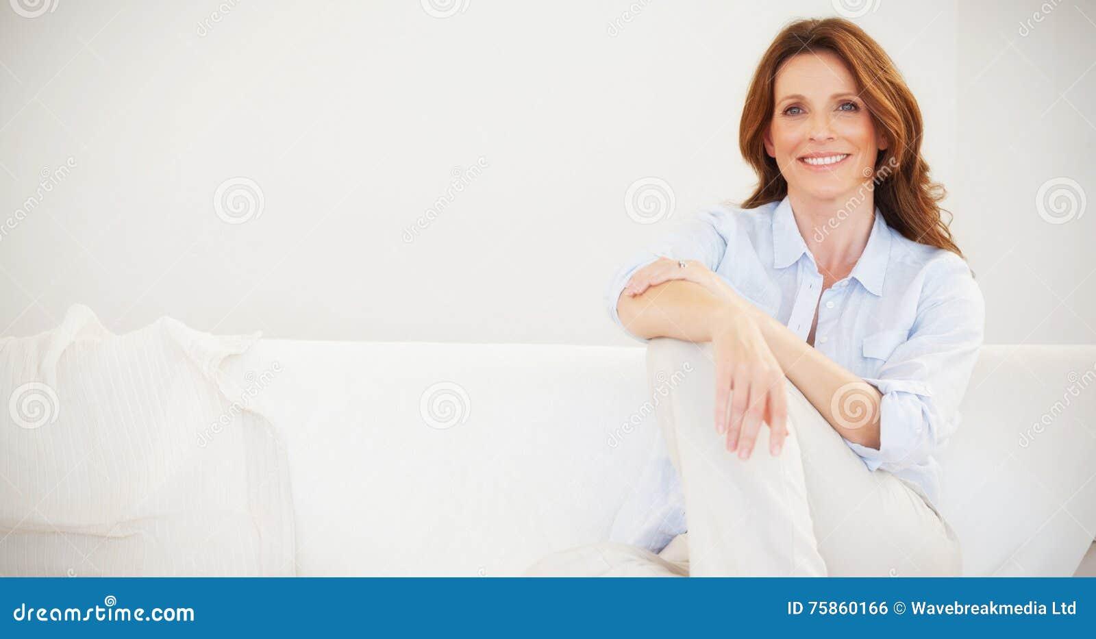 Συνεδρίαση γυναικών χαμόγελου ώριμη στον καναπέ