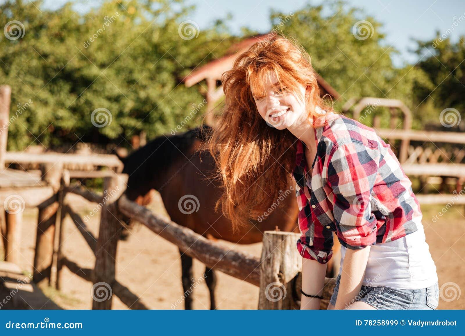 Συνεδρίαση γυναικών χαμόγελου cowgirl στο φράκτη στο χωριό