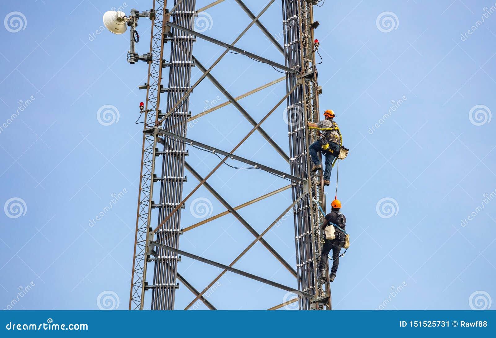 Συντήρηση τηλεπικοινωνιών Δύο άτομα επισκευής που αναρριχούνται στον πύργο στο κλίμα μπλε ουρανού