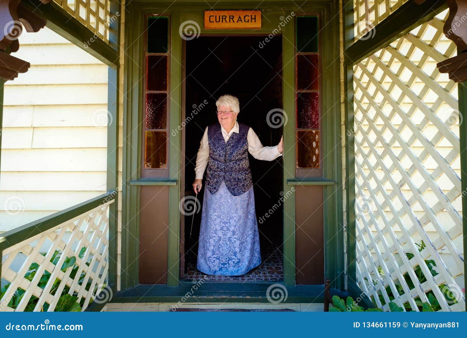 Συνταξιούχες ηλικιωμένες αγγλικές στάσεις γυναικών έξω από την πόρτα της