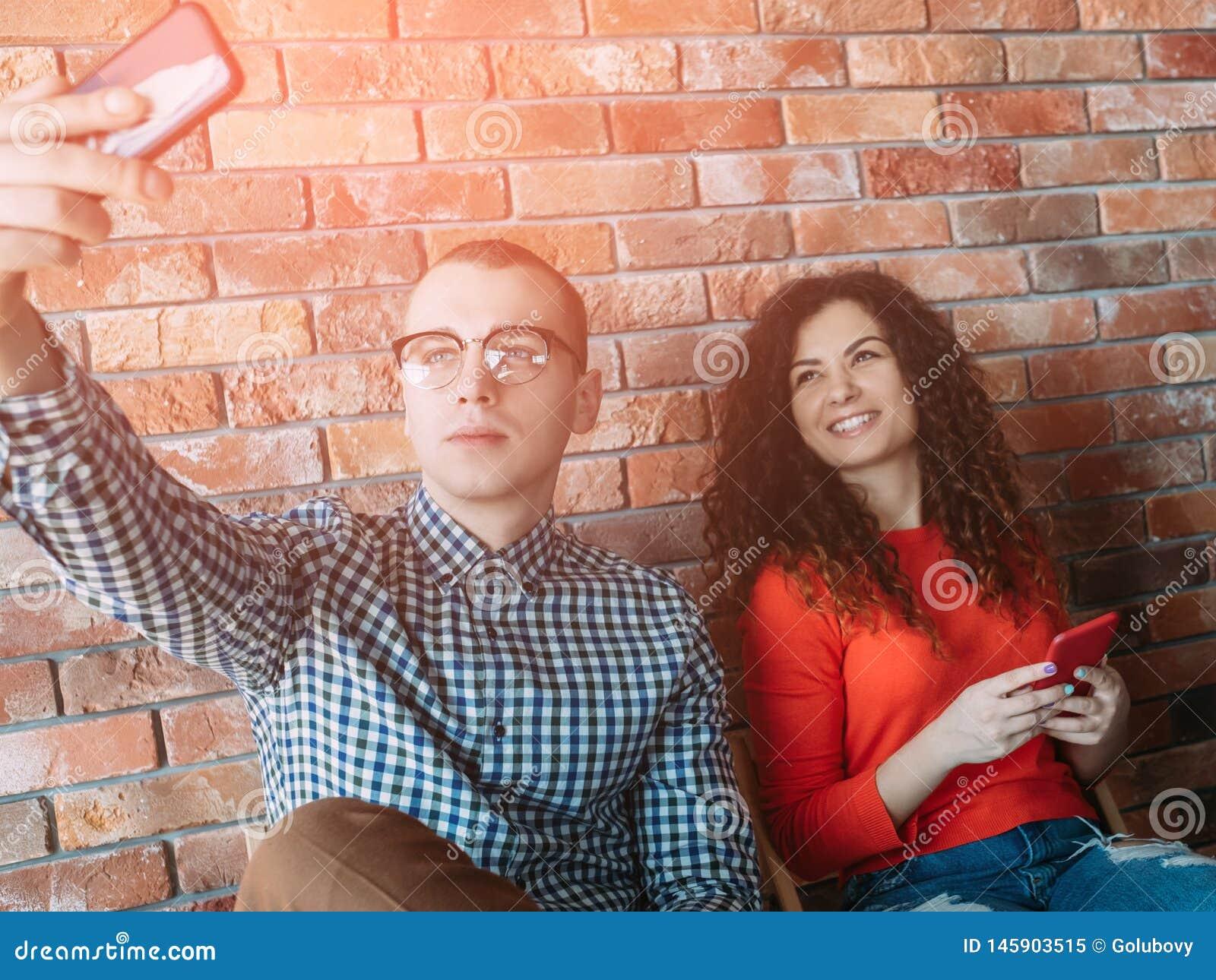 Συντριβή brunette γυναικών ανδρών smartphones nerd selfie