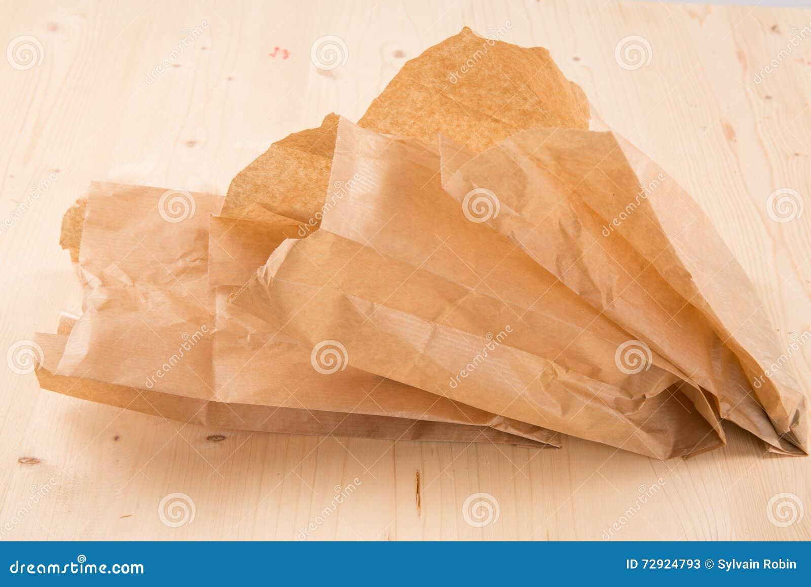 Συσκευάζοντας την ανακυκλωμένη σακούλα εγγράφου του Κραφτ στο ξύλινο υπόβαθρο με το ψαλίδισμα της πορείας