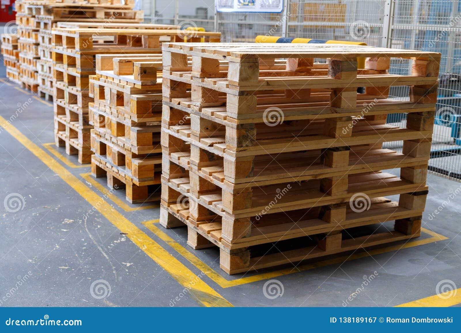 Συσσωρευμένες ξύλινες παλέτες σε μια αποθήκευση