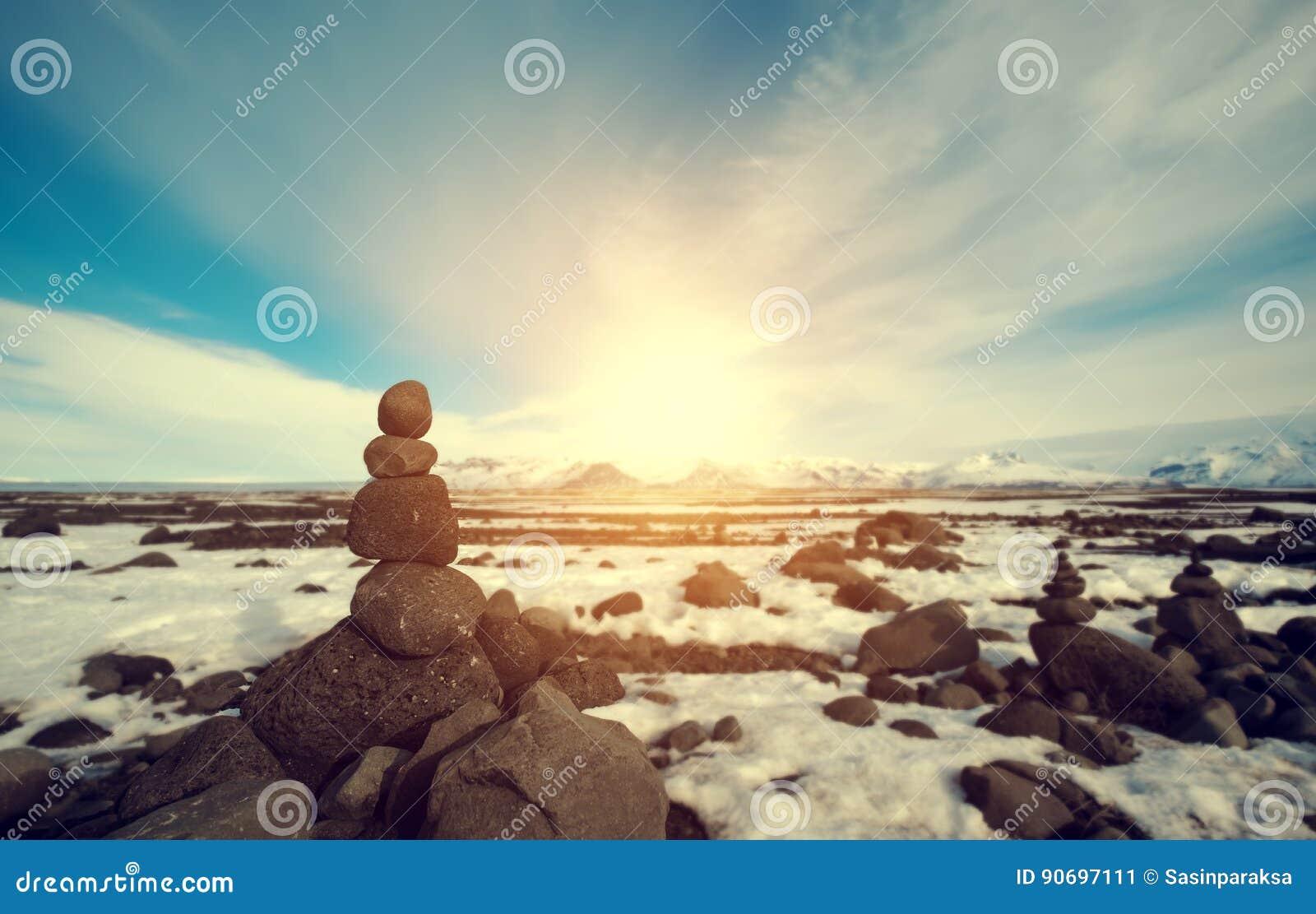 Συσσωρευμένη ο Stone ισορροπία στο χειμερινό τοπίο, με το φωτεινό φως του ήλιου