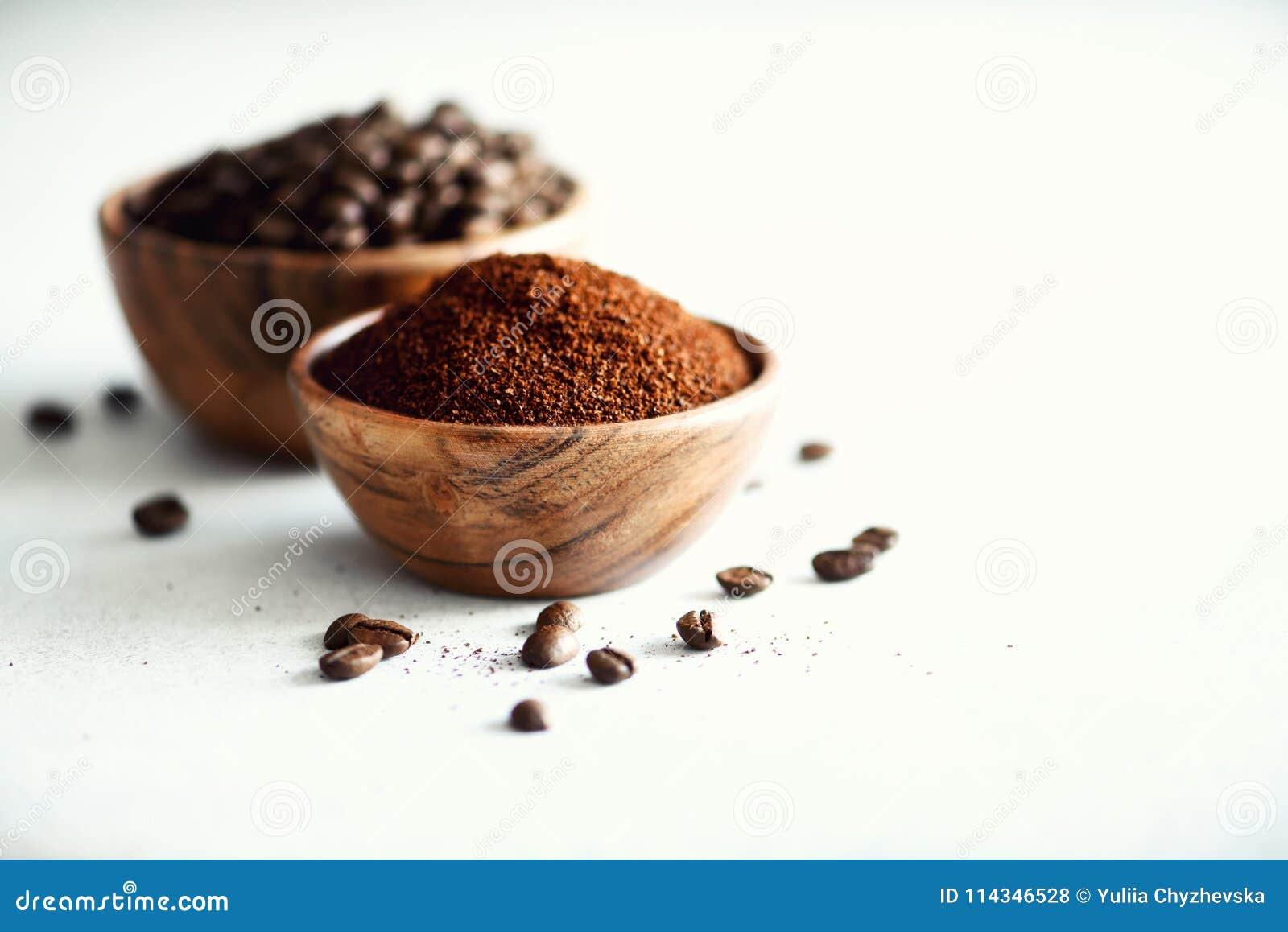 Συστατικά για την κατασκευή της καφεΐνης να πιει - φασόλια καφέ, έδαφος και στιγμιαίος καφές στο ελαφρύ συγκεκριμένο υπόβαθρο, δι