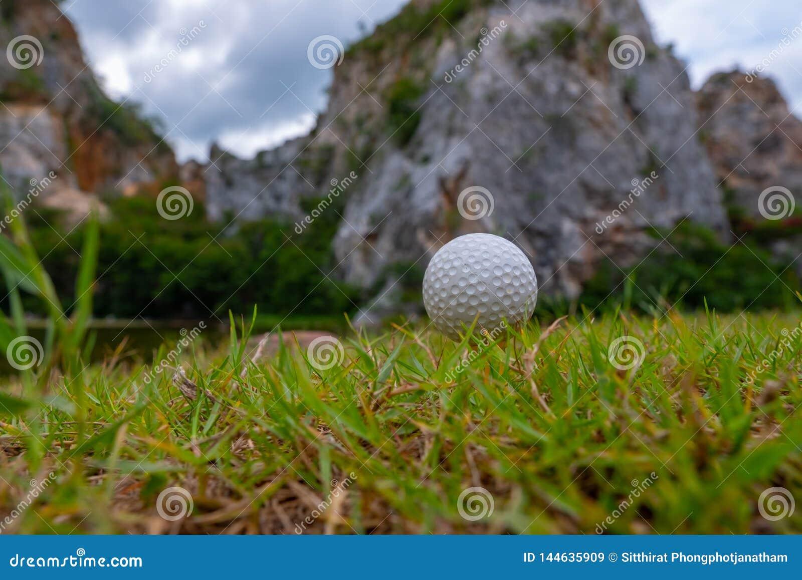 Σφαίρα γκολφ στη χλόη κοντά στο βουνό