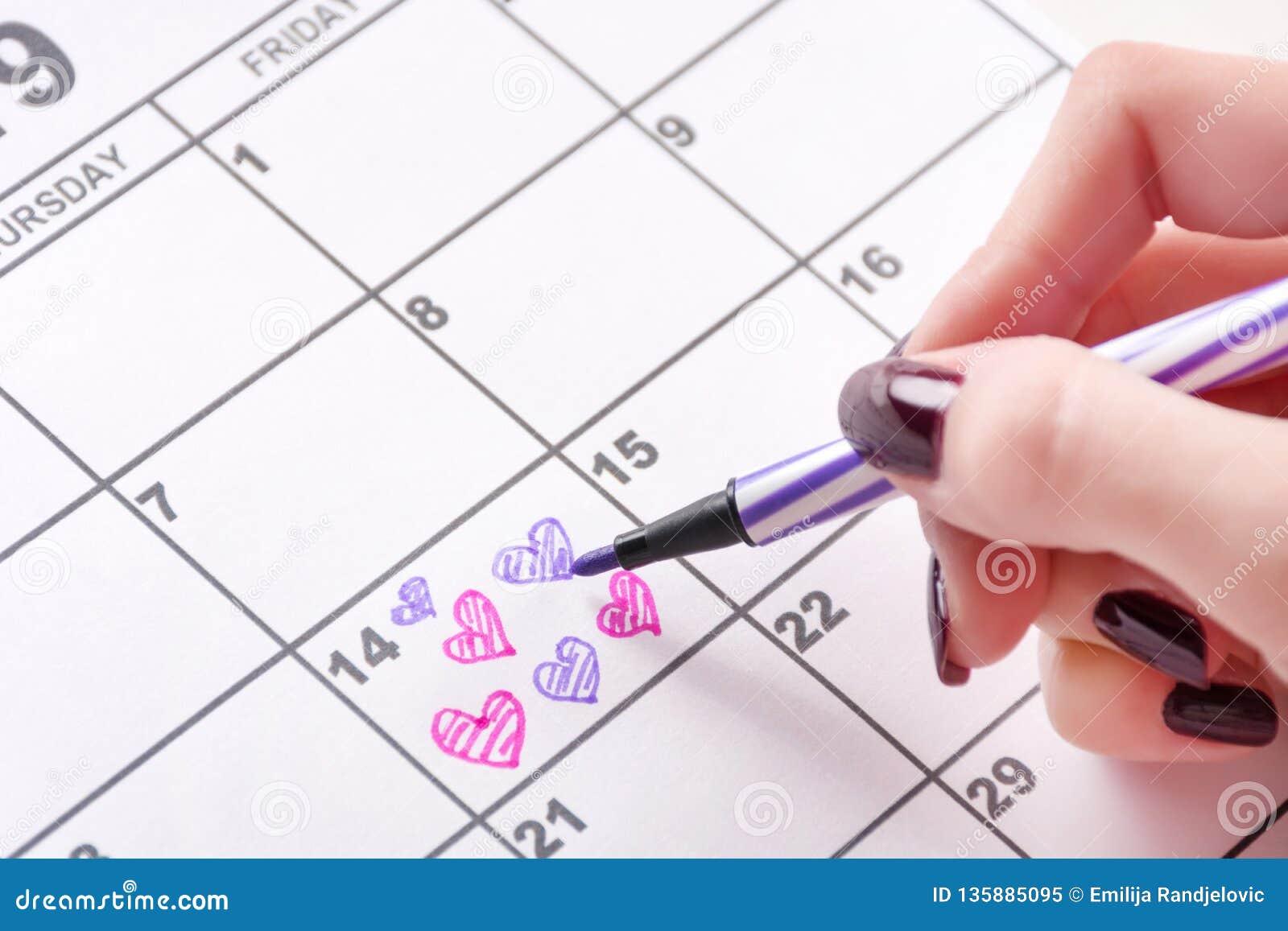 Σχεδιασμός χεριών κοριτσιών και μορφή καρδιών χρωματισμού στο ημερολόγιο για την ημέρα βαλεντίνων με την αισθητή μάνδρα