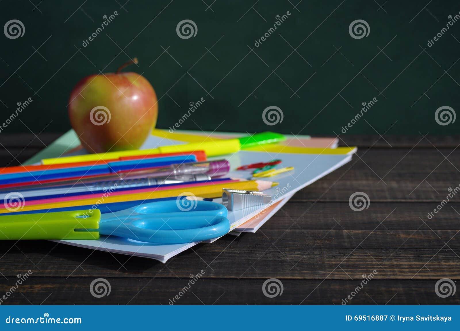 Σχολικές προμήθειες σε έναν ξύλινο πίνακα ενάντια σε έναν πίνακα