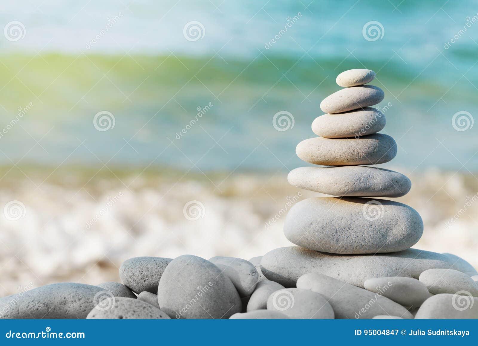 Σωρός της άσπρης πέτρας χαλικιών στο μπλε κλίμα θάλασσας για τη SPA, την ισορροπία, την περισυλλογή και zen το θέμα