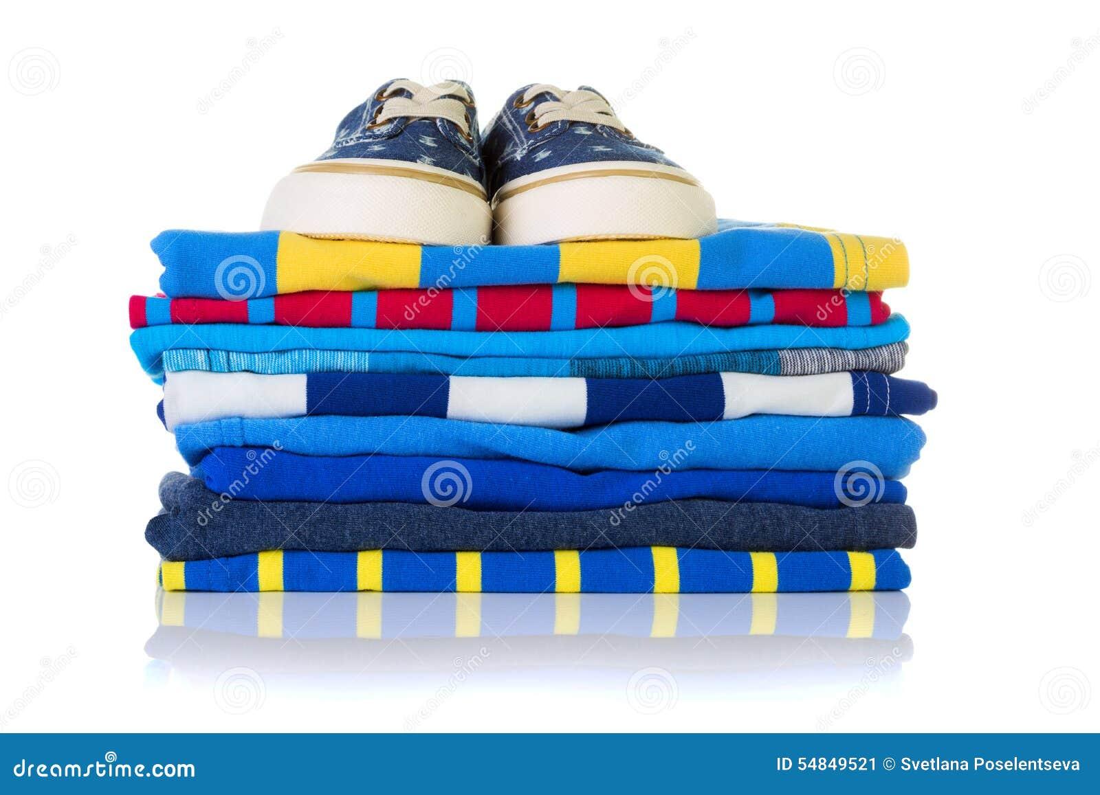 Σωρός των ζωηρόχρωμων θερινών πουκάμισων και ένα ζευγάρι των πάνινων παπουτσιών στην κορυφή ι