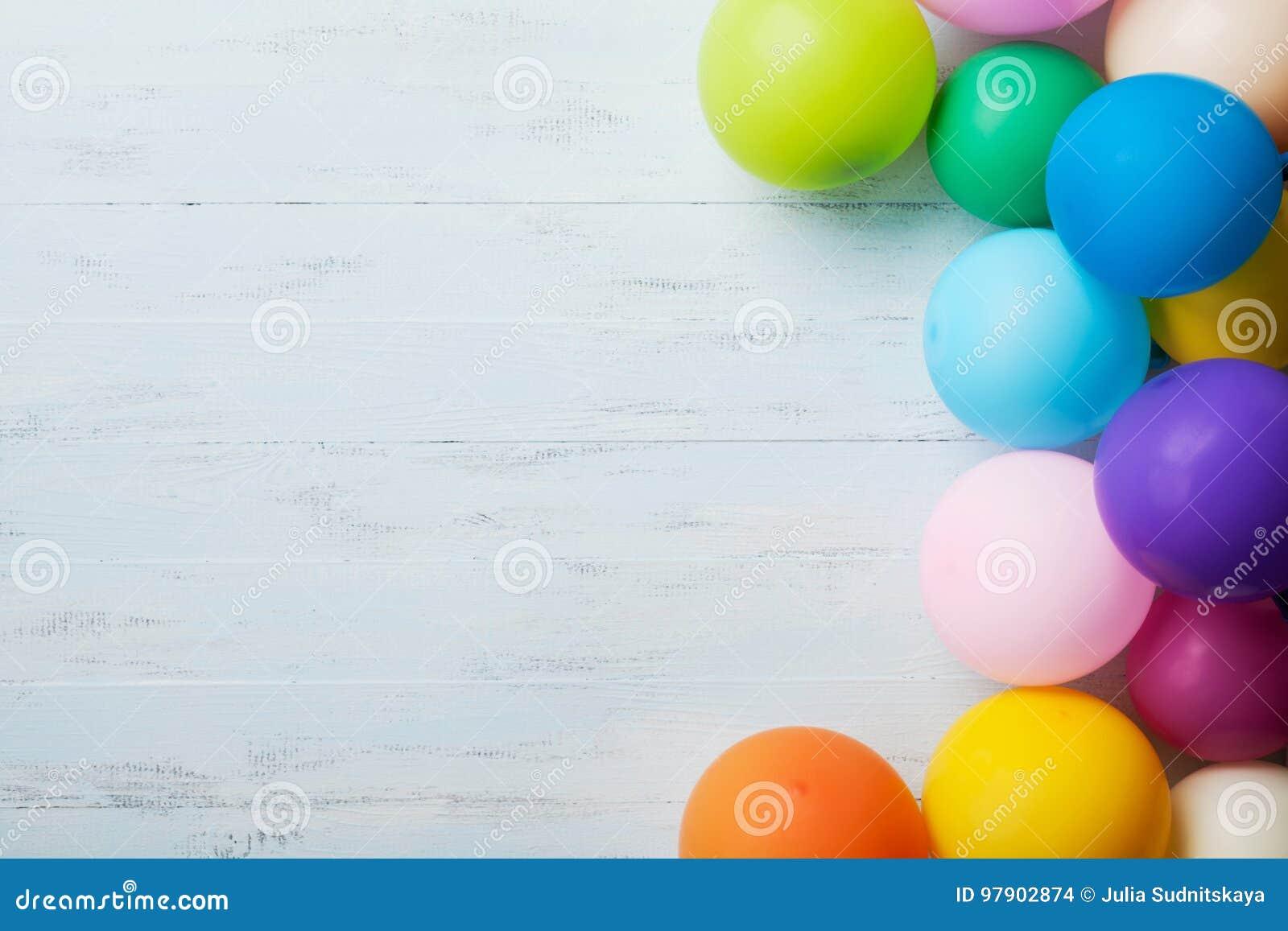 Σωρός των ζωηρόχρωμων μπαλονιών στην μπλε ξύλινη άποψη επιτραπέζιων κορυφών η συνημμένη κάρτα κιβωτίων γενεθλίων ανασκόπησης πολλ