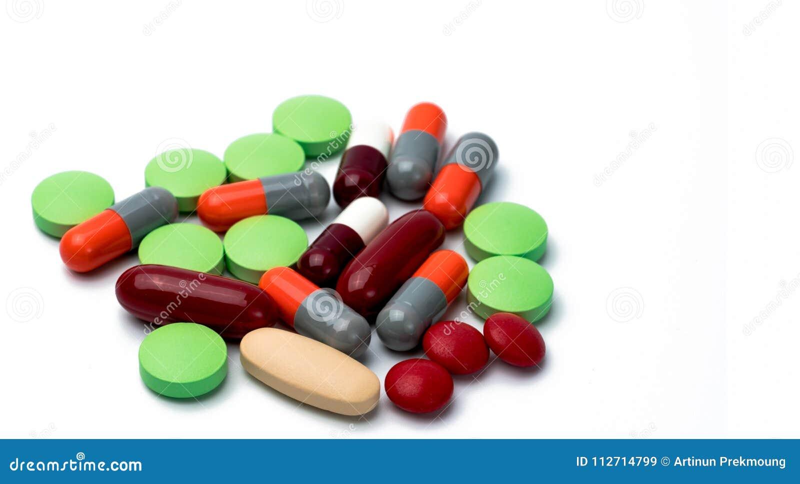 Σωρός των ζωηρόχρωμων ταμπλετών και των χαπιών καψών που απομονώνονται στο άσπρο υπόβαθρο Φάρμακο, βιταμίνη, συμπλήρωμα και βοταν