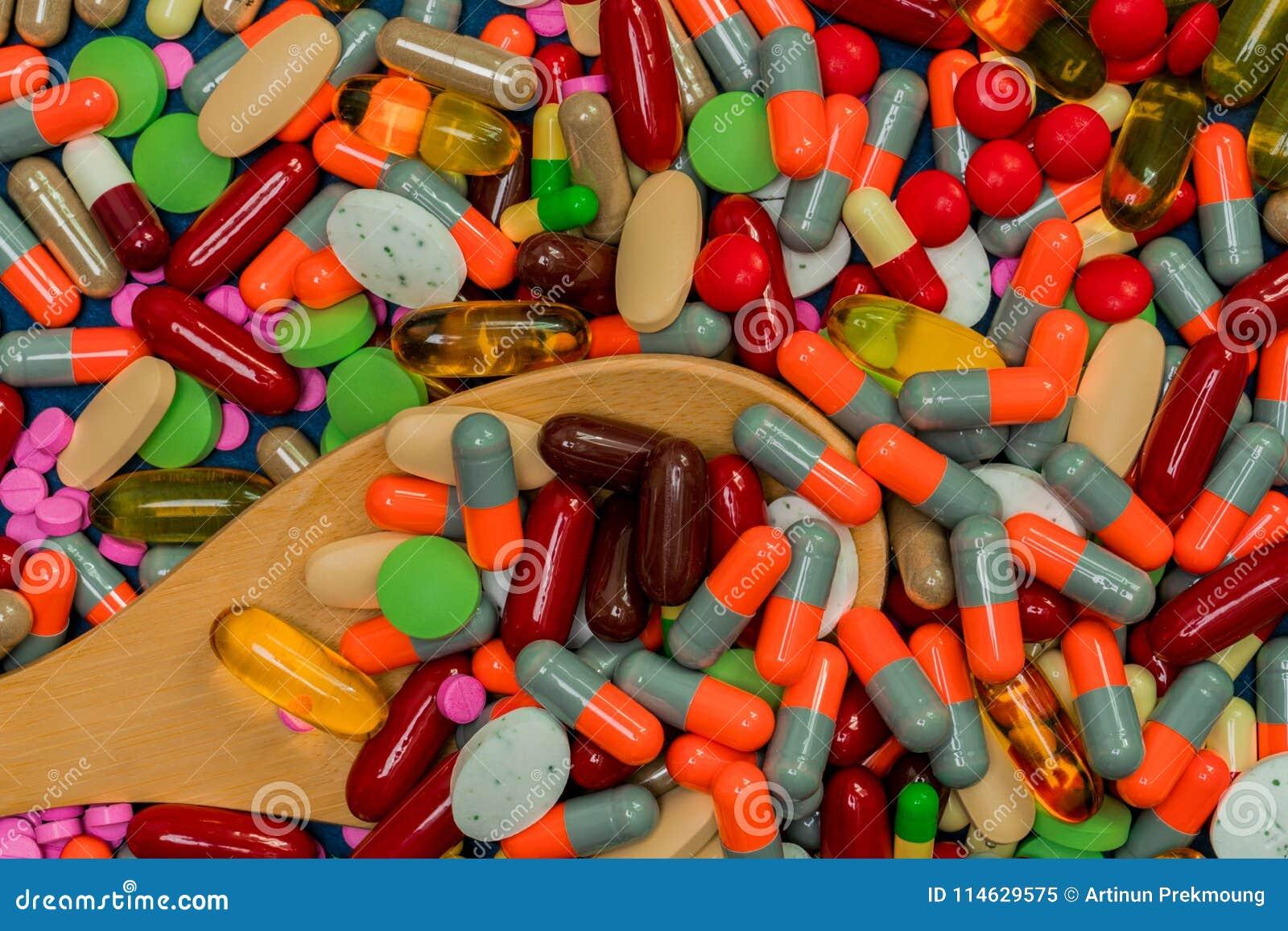 Σωρός των ζωηρόχρωμων χαπιών και του ξύλινου κουταλιού Ιατρική, βιταμίνες, συμπλήρωμα και ανόργανα άλατα Αντίσταση φαρμάκων αντιβ