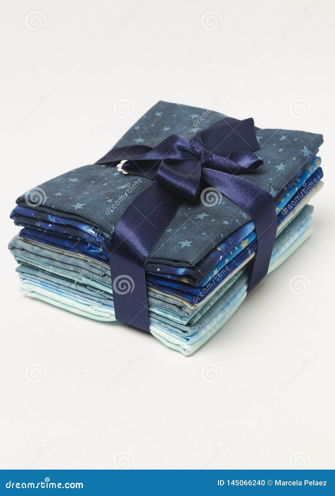 Σωρός των μπλε διπλωμένων σκιές υφασμάτων με την κορδέλλα δώρων άνωθε