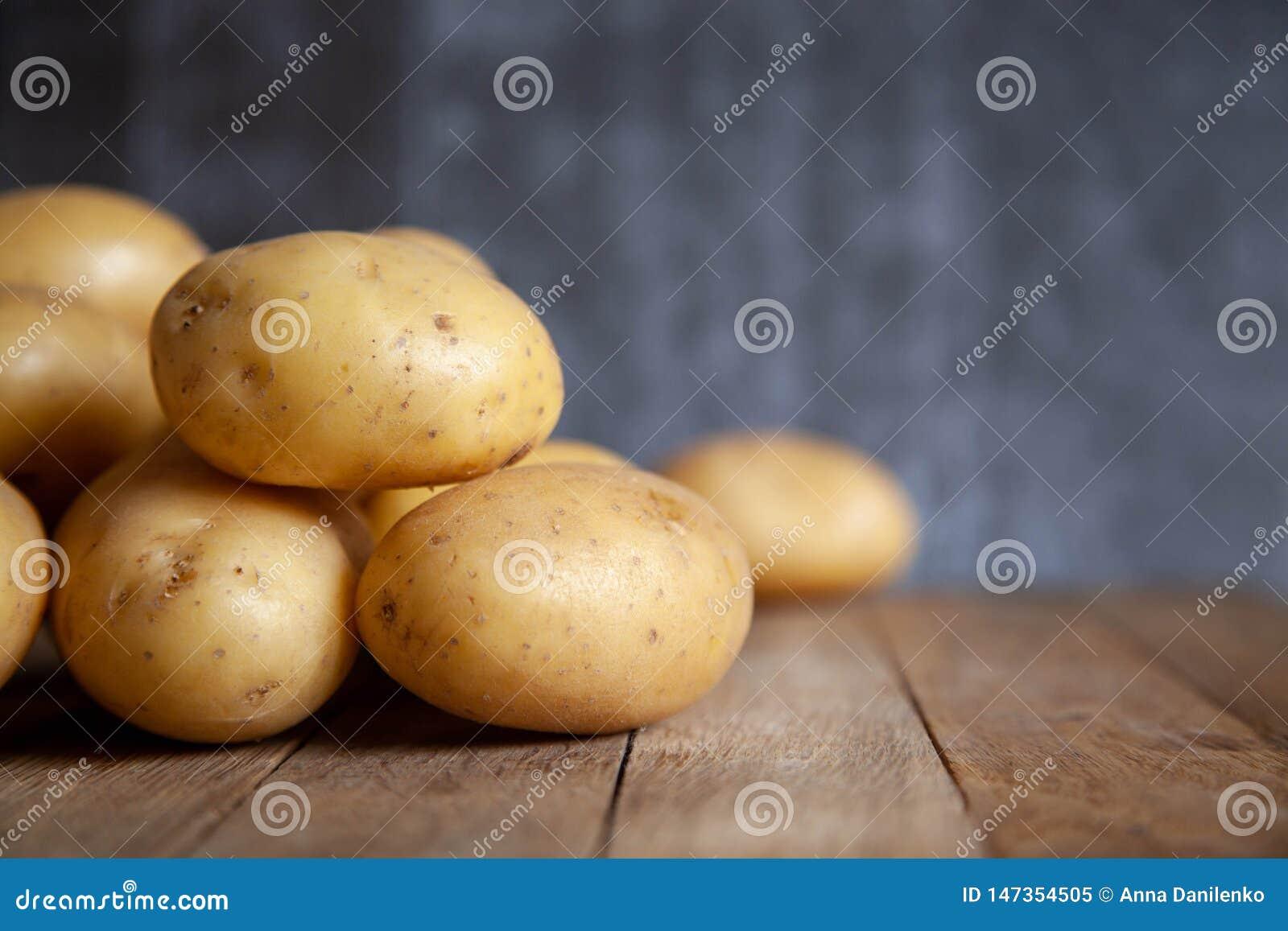 Σωρός των πατατών στον παλαιό ξύλινο πίνακα
