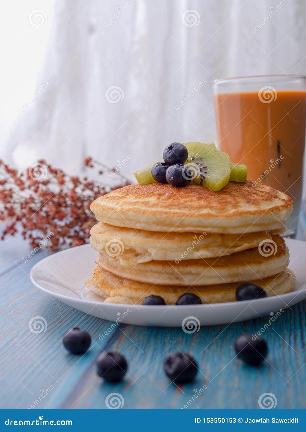 Σωρός των τηγανιτών με το κάλυμμα, το ακτινίδιο και το βακκίνιο τοποθετημένος σε ένα άσπρο πιάτο σε έναν μπλε ξύλινο πίνακα Φάτε