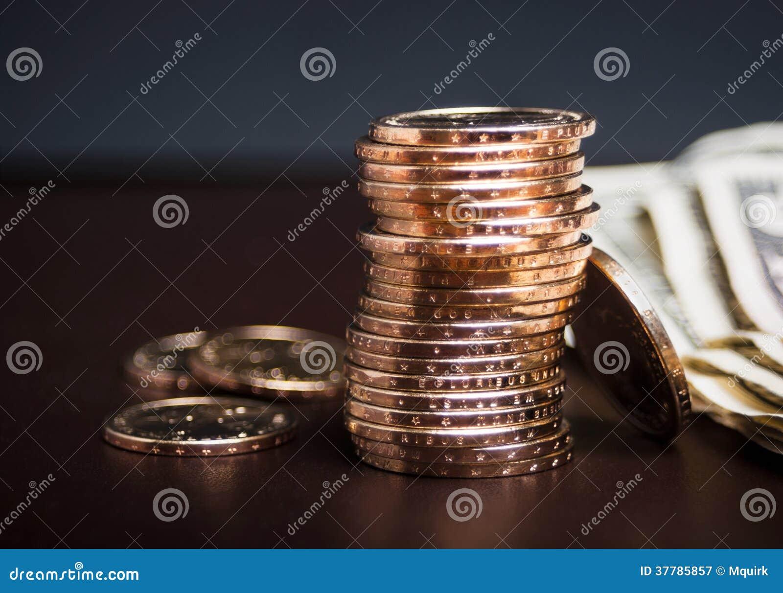 Σωρός των χρυσών νομισμάτων με τα μετρητά
