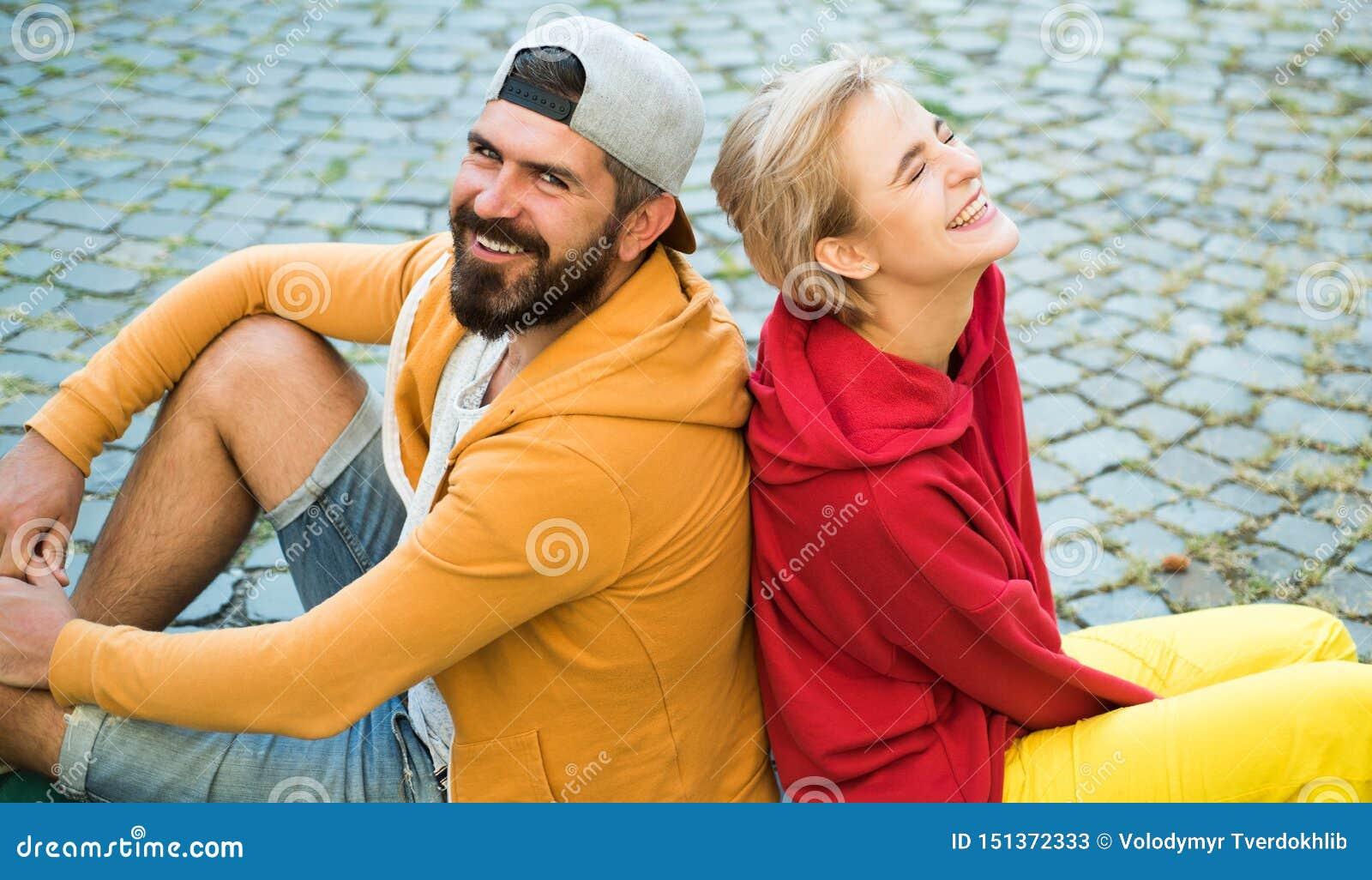 Σύγχρονα ενδύματα ανδρών και γυναικών για τη νεολαία που χαλαρώνει υπαίθρια Για πάντα νέος Το ζεύγος κρεμά έξω από κοινού Ξένοιασ