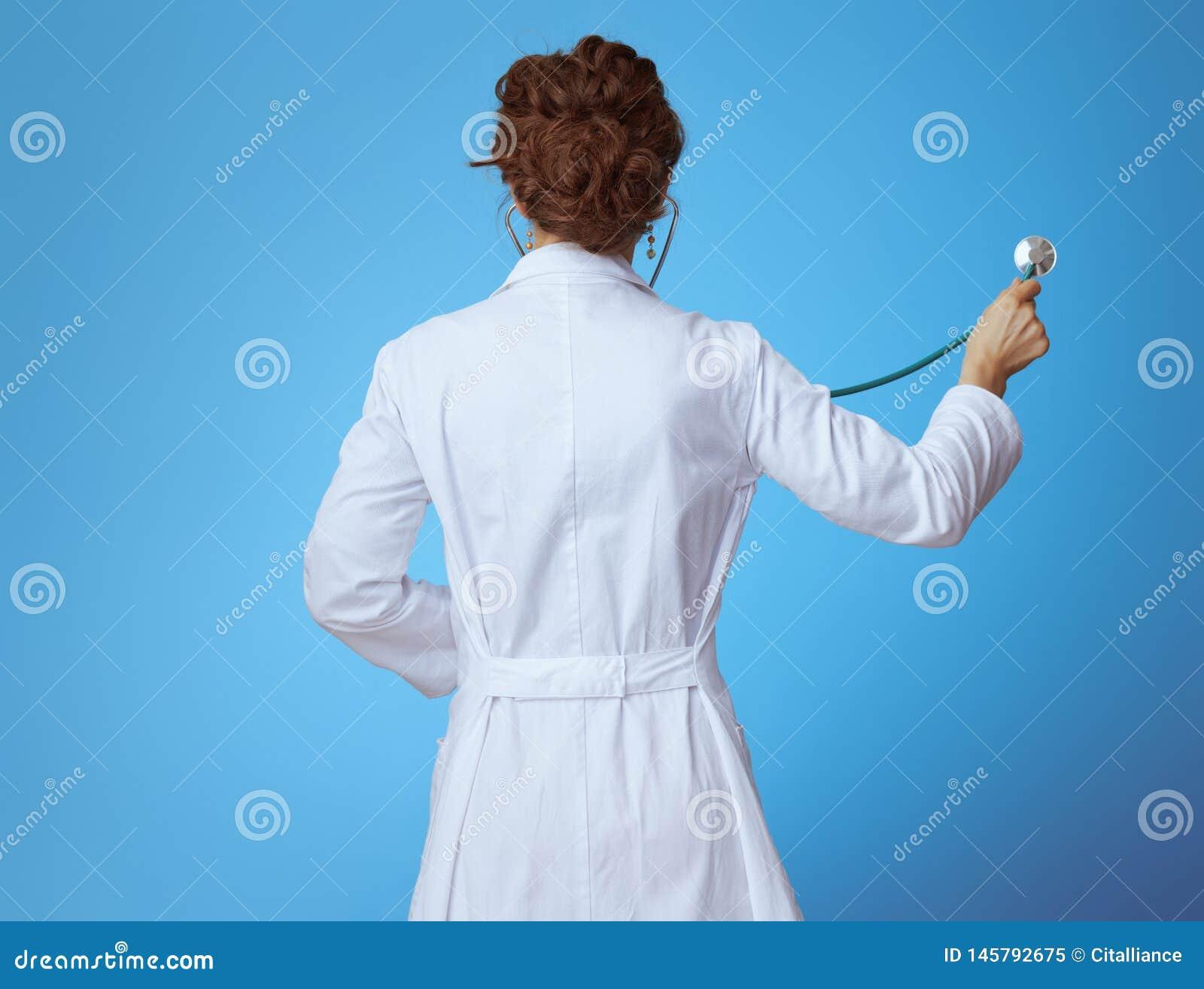 Σύγχρονη γυναίκα ιατρών που ακούει με το στηθοσκόπιο στο μπλε