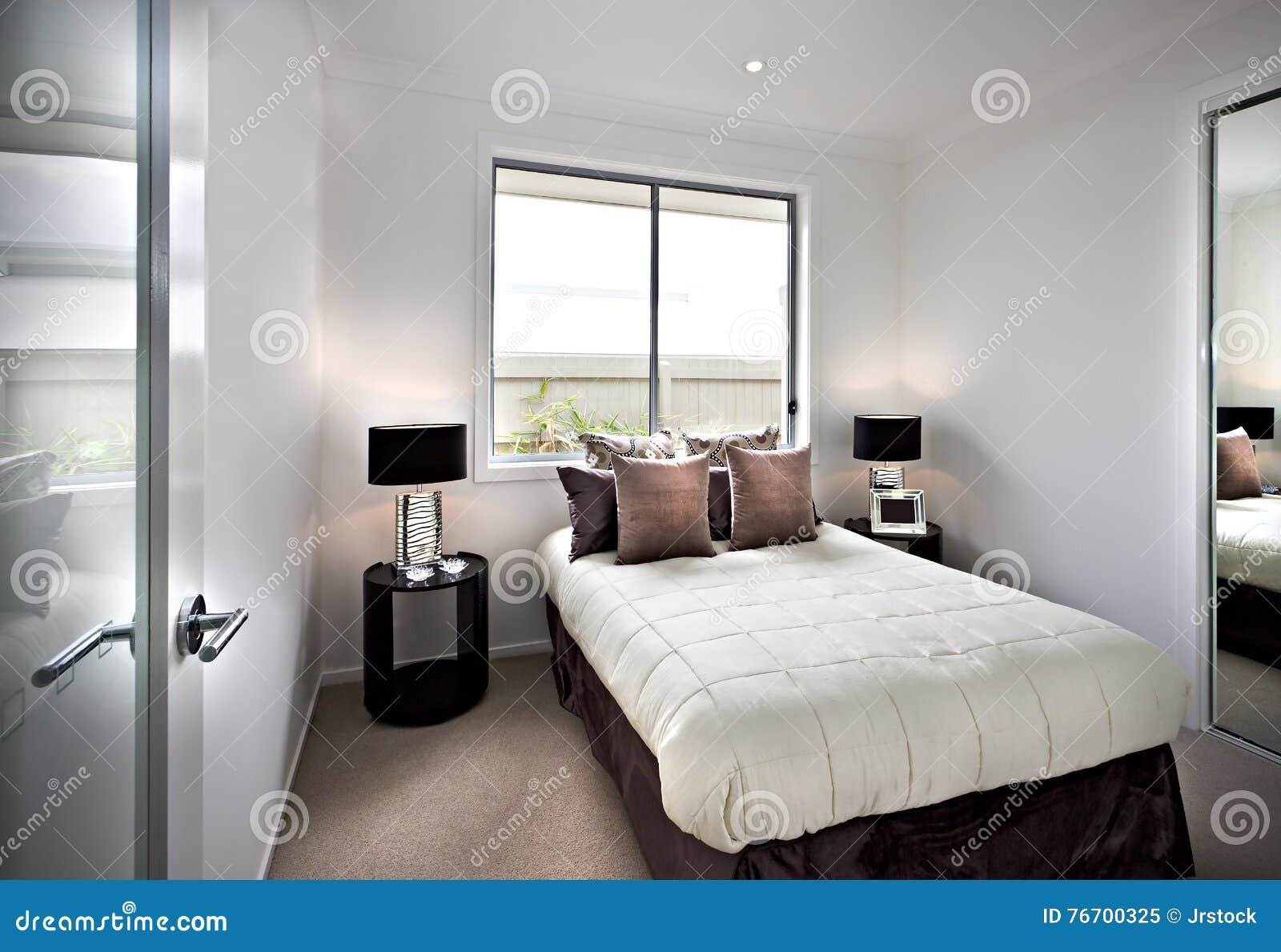 Σύγχρονη και κλασική κρεβατοκάμαρα με τα παράθυρα και τους λαμπτήρες