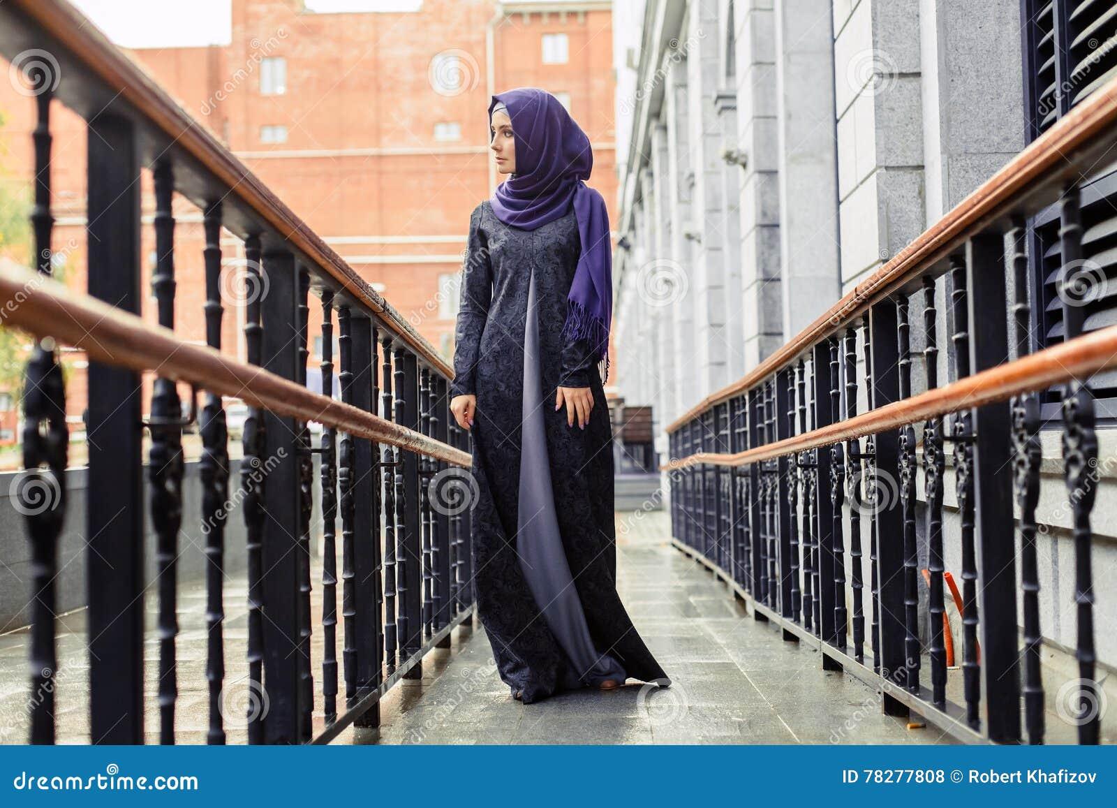 Σύγχρονη μουσουλμανική γυναίκα στο όμορφο ανατολικό φόρεμα που στέκεται στο υπόβαθρο του ξενοδοχείου