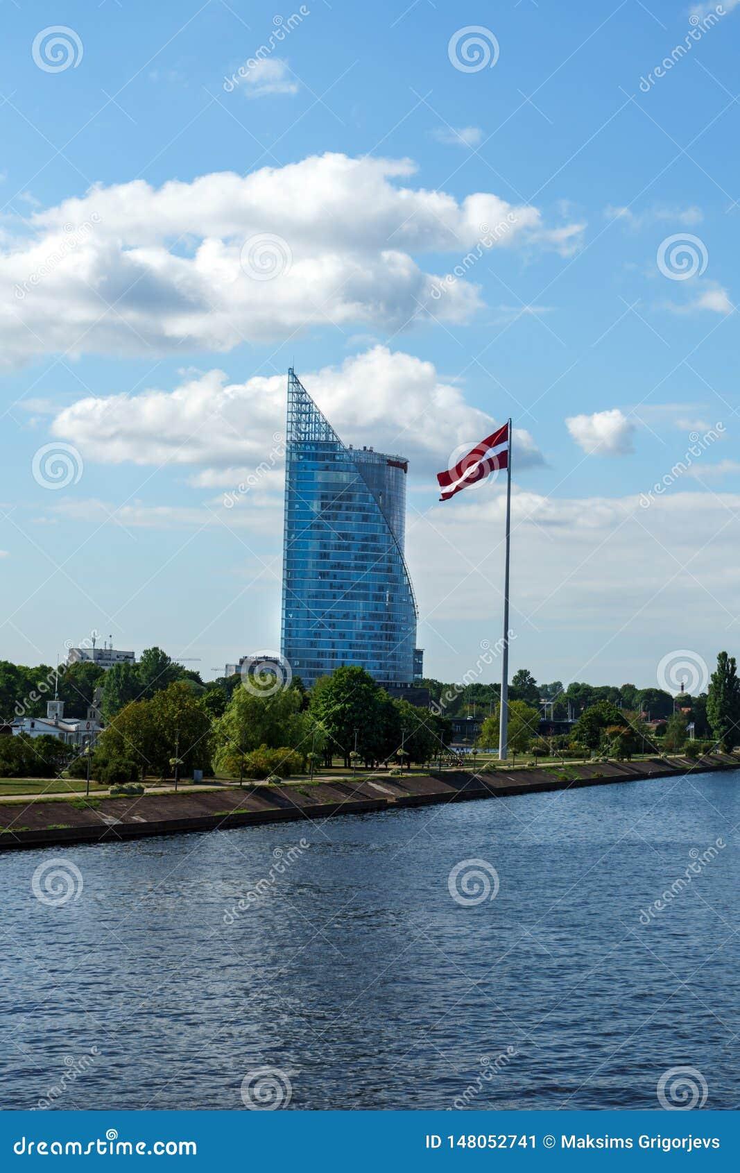 Σύγχρονος ουρανοξύστης γυαλιού του γραφείου Swedbank και της λετονικής σημαίας ενάντια στο μπλε ουρανό στην πόλη της Ρήγας, Λετον