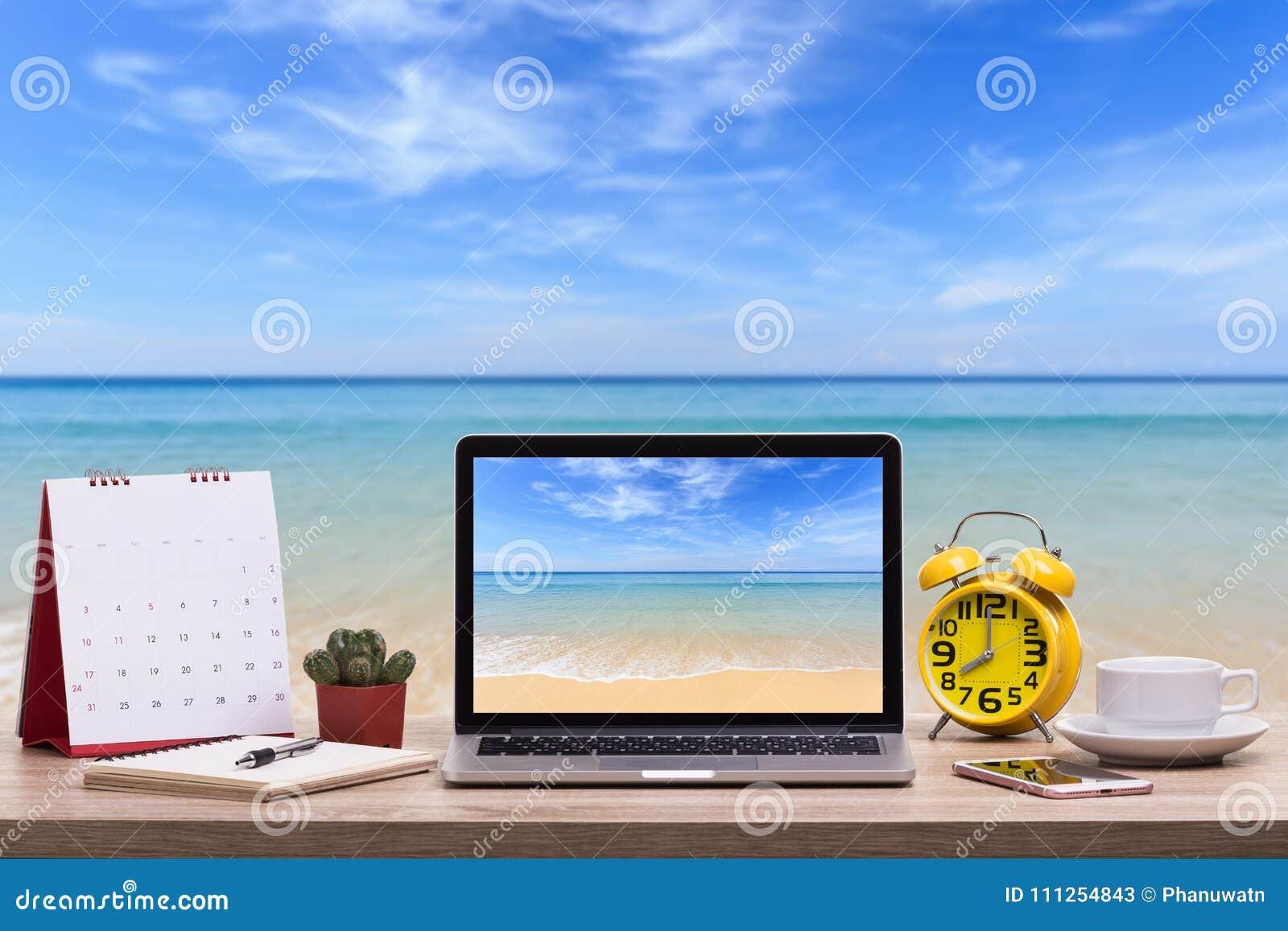 Σύγχρονος φορητός προσωπικός υπολογιστής, φλυτζάνι καφέ, ξυπνητήρι, σημειωματάριο και ασβέστιο
