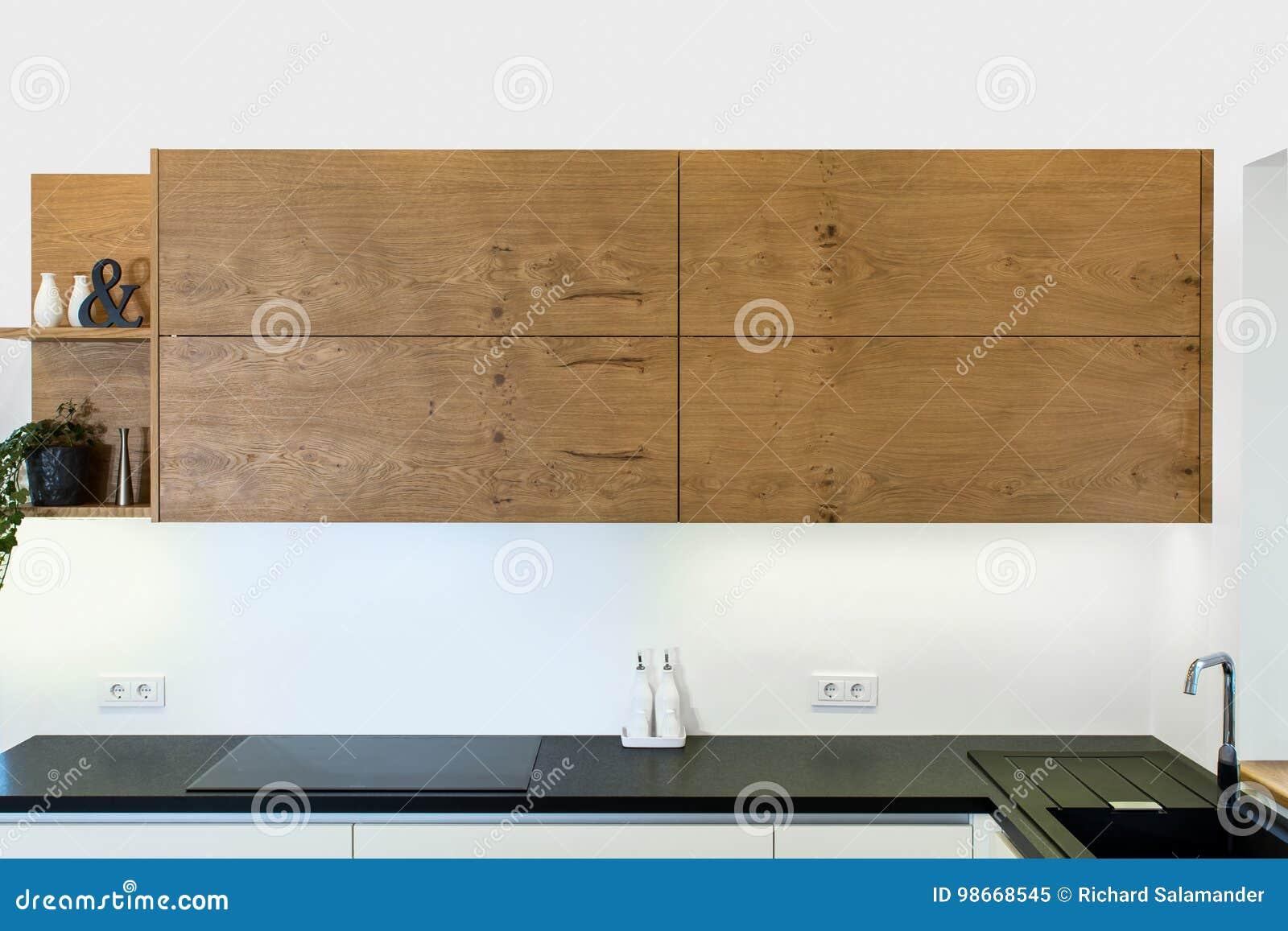 Σύγχρονο σχέδιο κουζινών στο ελαφρύ εσωτερικό με τις ξύλινες εμφάσεις