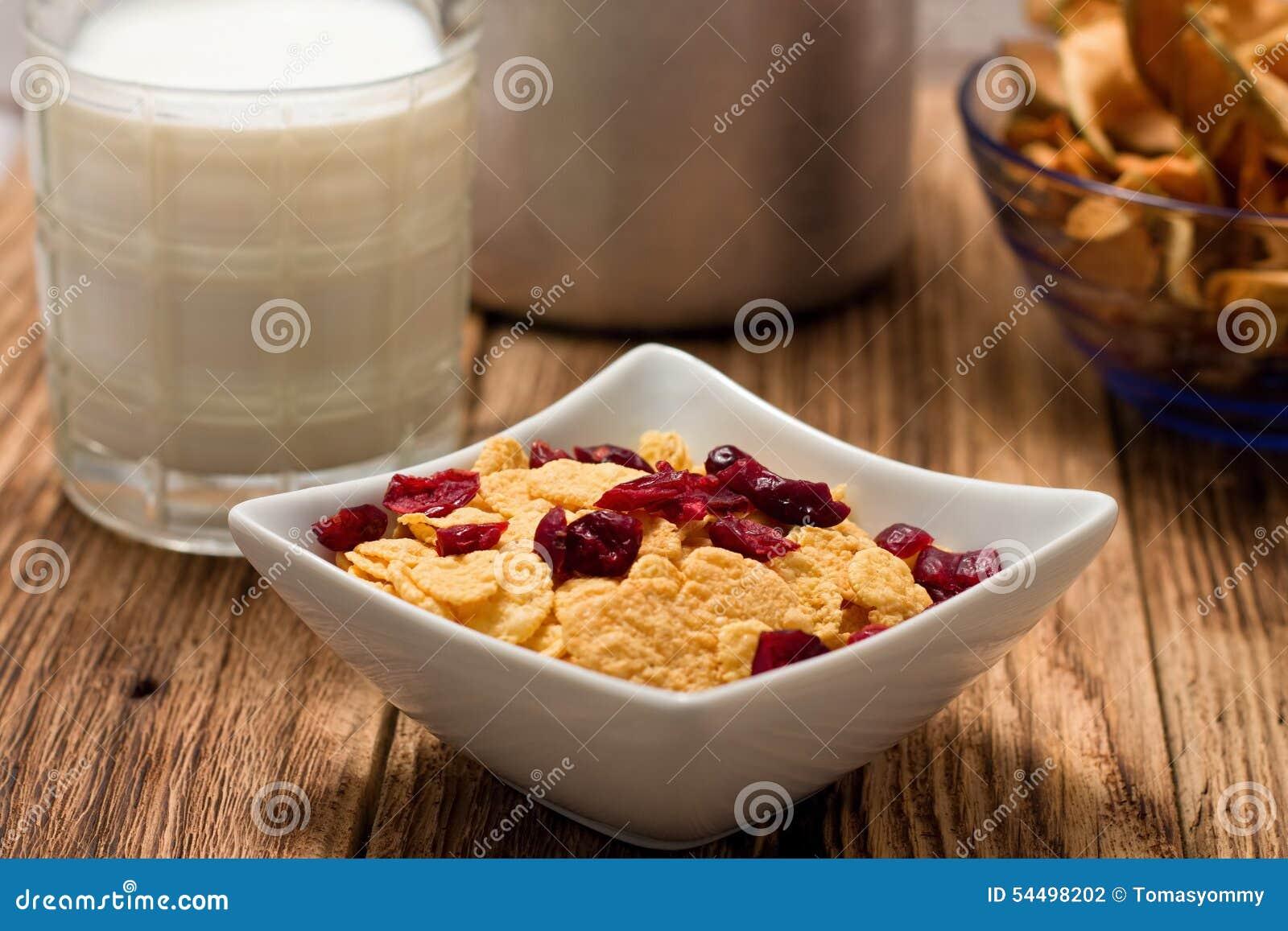 Σύγχρονο τετραγωνικό κύπελλο με τα δημητριακά μπροστά από το ποτήρι του γάλακτος