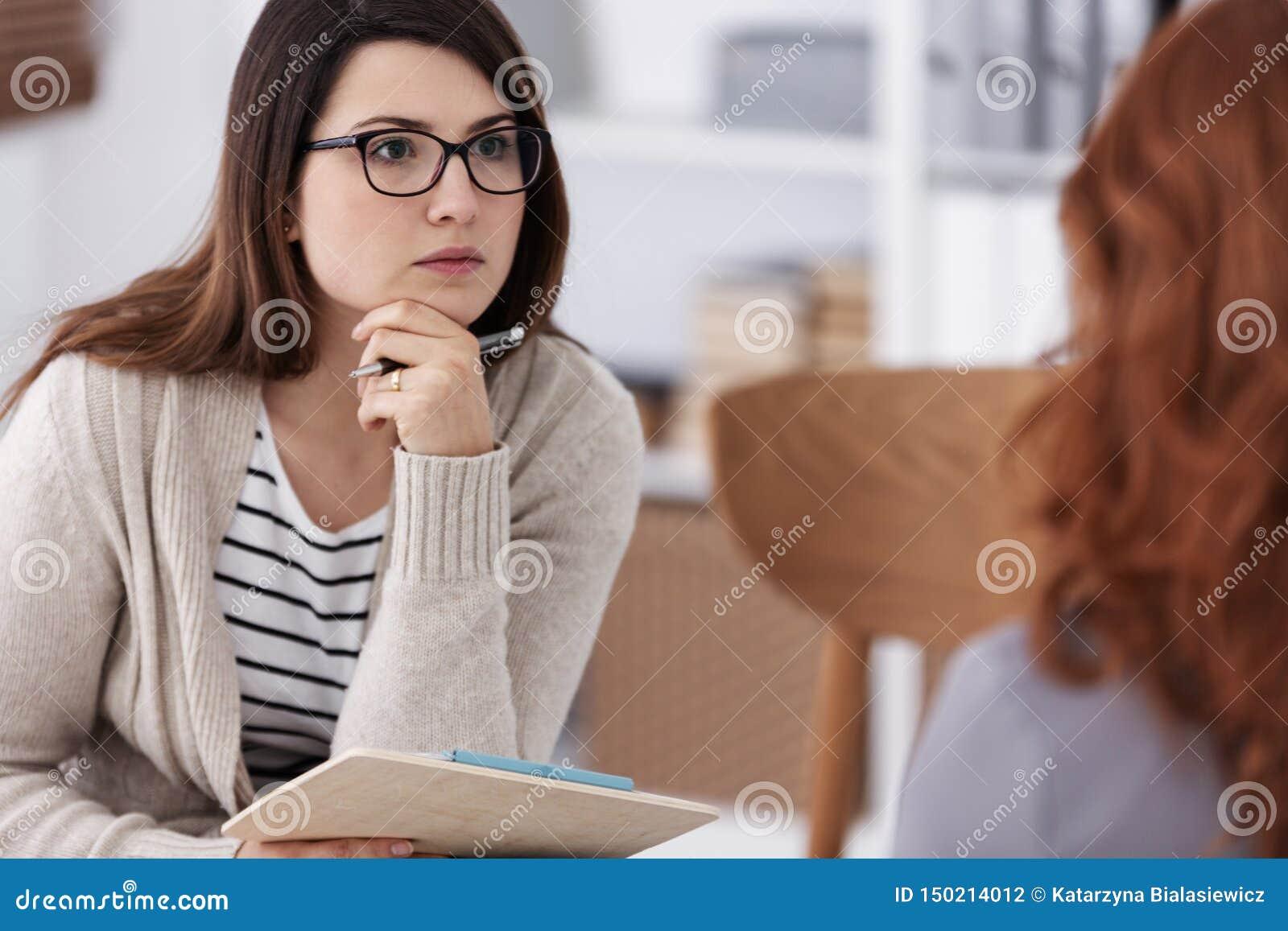 Σύμβουλος Profesional με το σημειωματάριο και μάνδρα κατά τη διάρκεια των γυναικών μορφής συνόδου εργαστηρίων