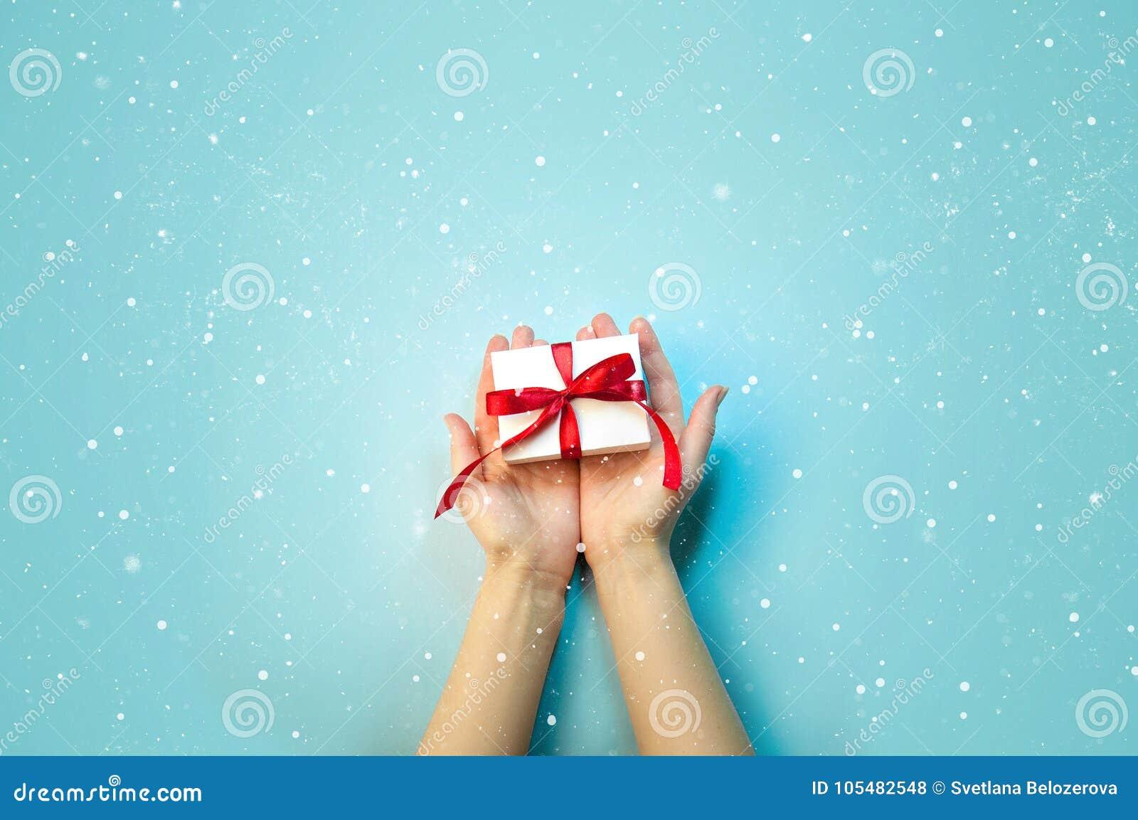 Σύνθεση διακοπών Χριστουγέννων Το νέο δώρο έτους στο άσπρο κιβώτιο με την κόκκινη κορδέλλα στα θηλυκά χέρια στο ανοικτό μπλε επίπ