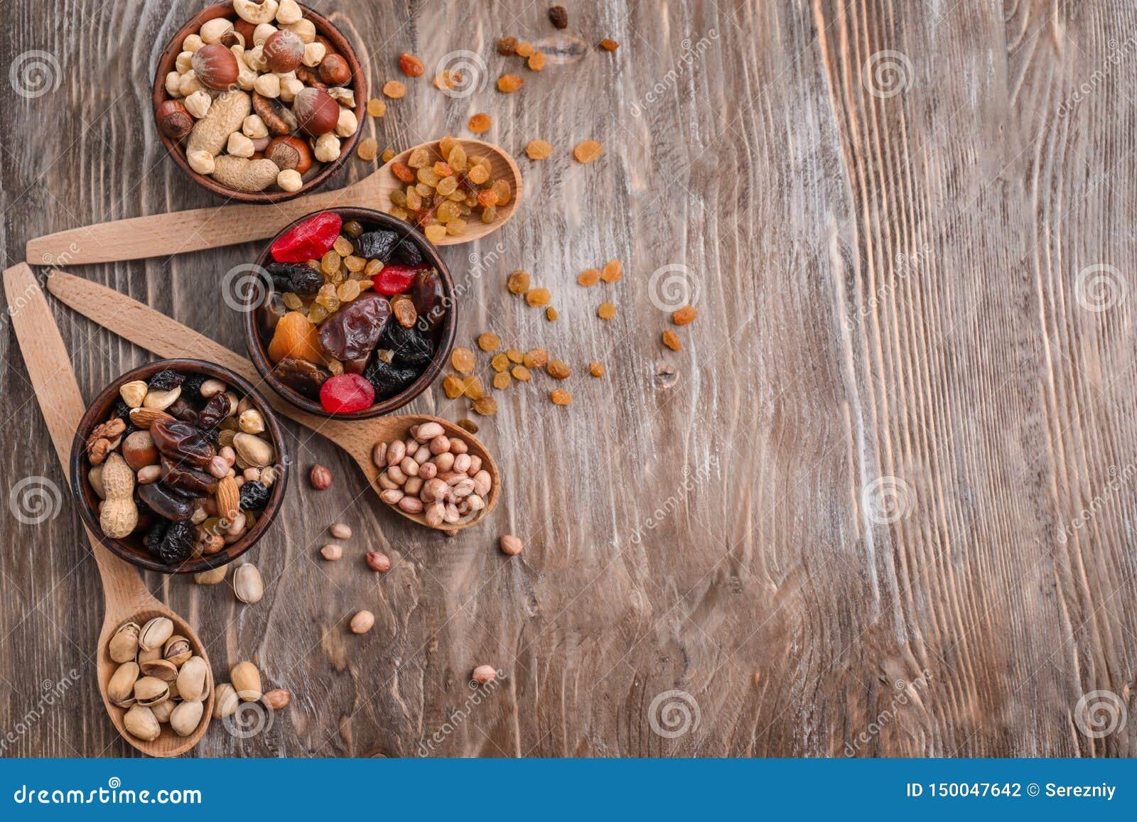 Σύνθεση με τα διαφορετικά είδη καρυδιών, ξηρών καρπών και μούρων στο ξύλινο υπόβαθρο