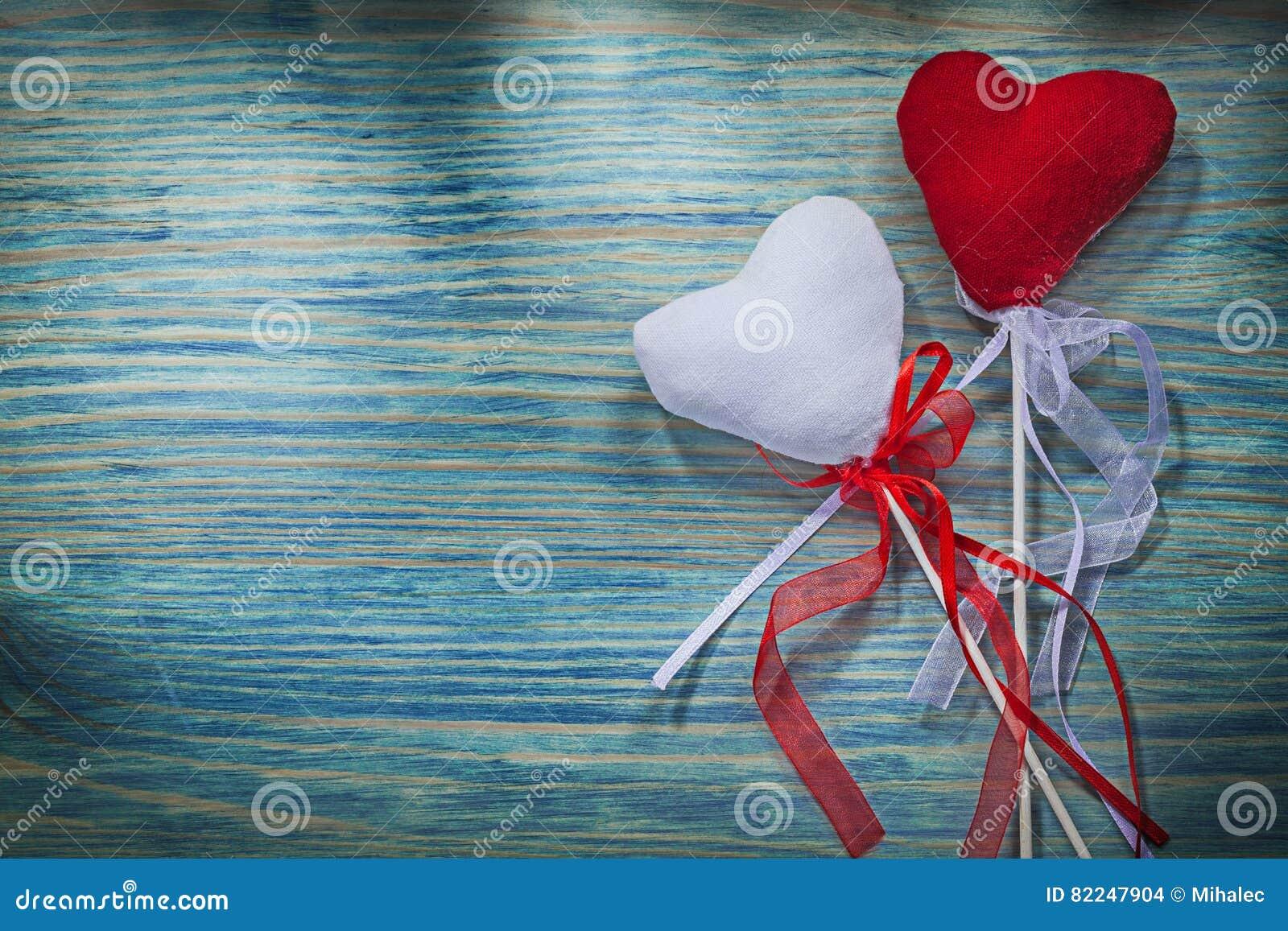Σύνθεση των κόκκινων και άσπρων καρδιών βαλεντίνων με τις κορδέλλες στο wo