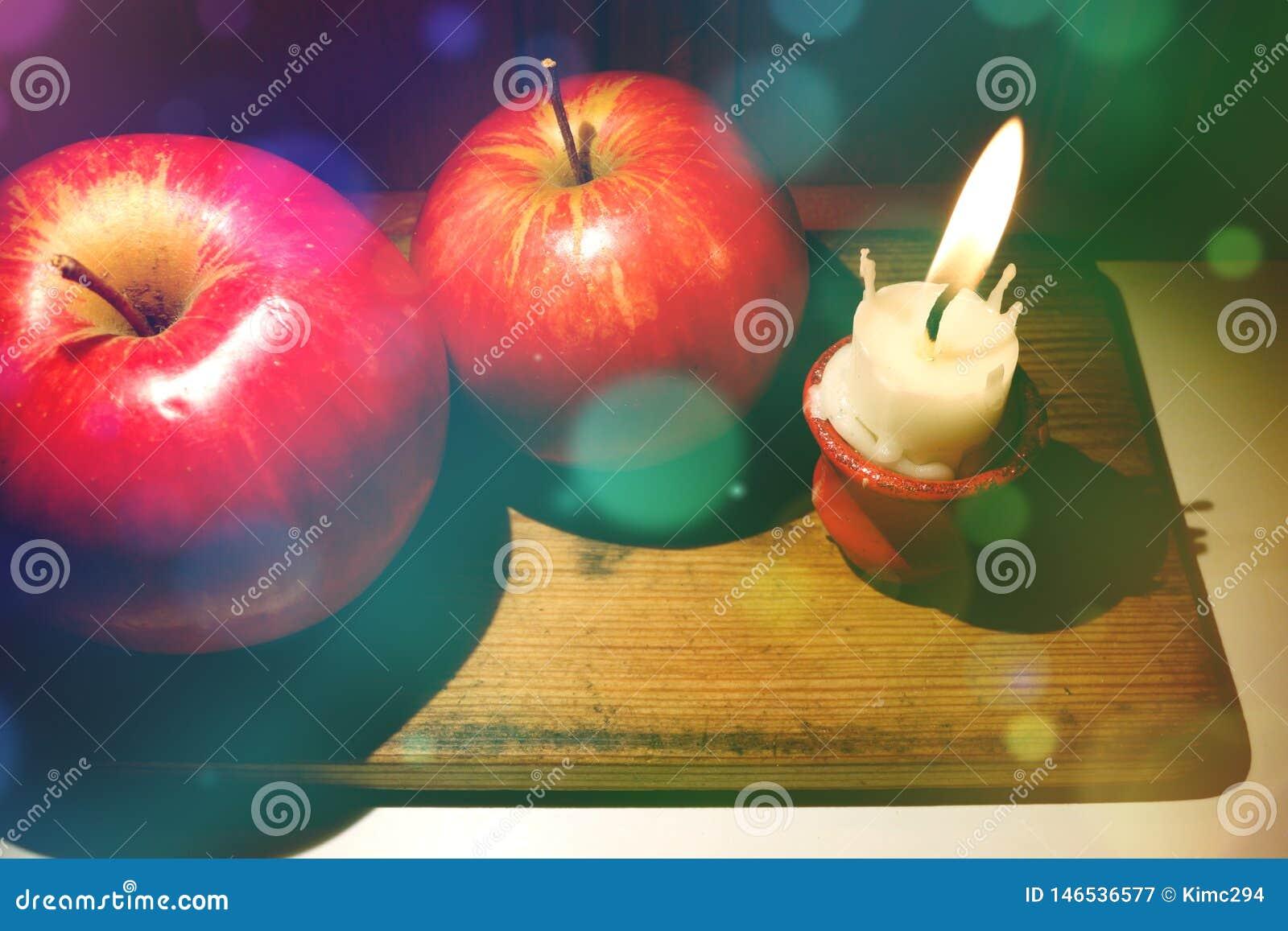 Σύνθεση Χριστουγέννων με τα κόκκινα μήλα και μικροσκοπικός που καίγεται κάτω από το κερί