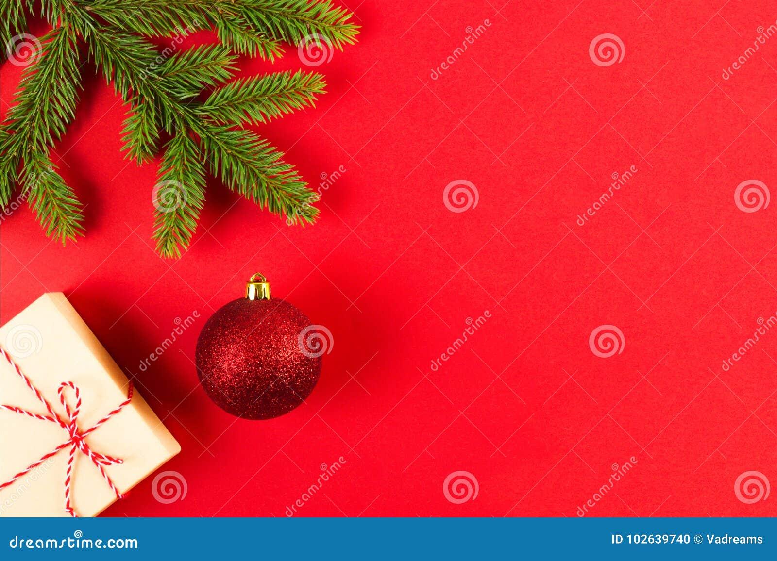 Σύνθεση Χριστουγέννων στο κόκκινο υπόβαθρο Πράσινοι κλάδοι δέντρων έλατου, παρούσες κιβώτιο Χριστουγέννων και διακόσμηση