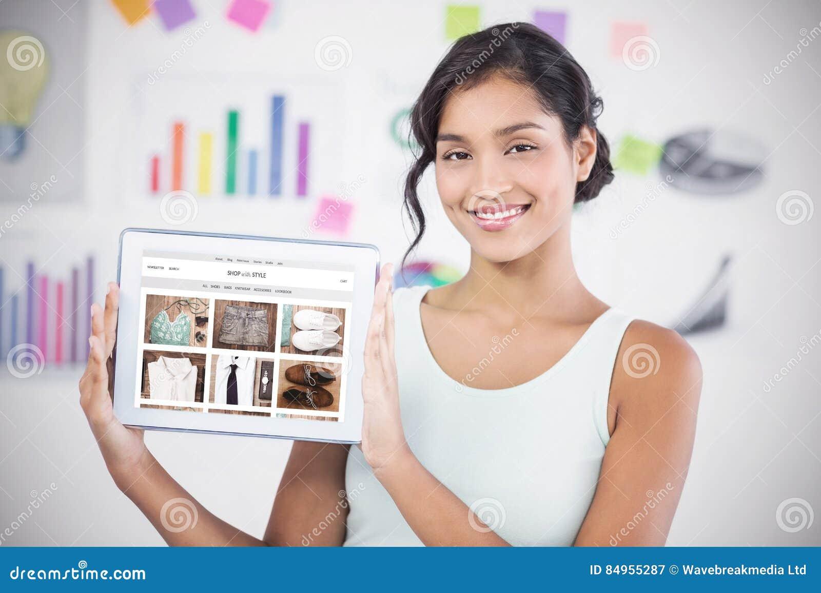 Σύνθετη εικόνα της ευτυχούς επιχειρηματία που παρουσιάζει ψηφιακή ταμπλέτα στο δημιουργικό γραφείο