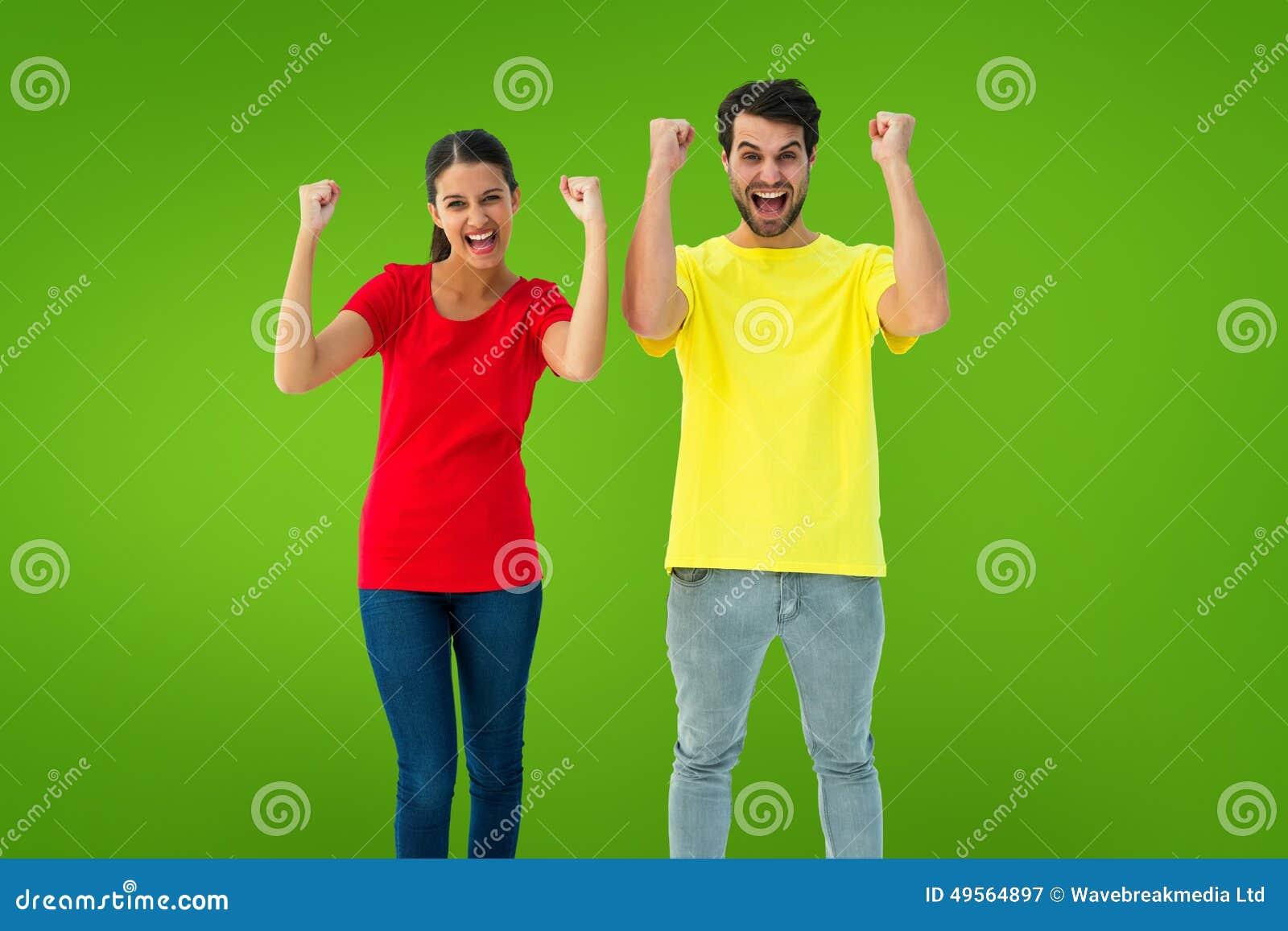 f35e2778e280 Συγκινημένο ζεύγος ενθαρρυντικό στις κόκκινες και κίτρινες μπλούζες ενάντια  στο πράσινο σύντομο χρονογράφημα