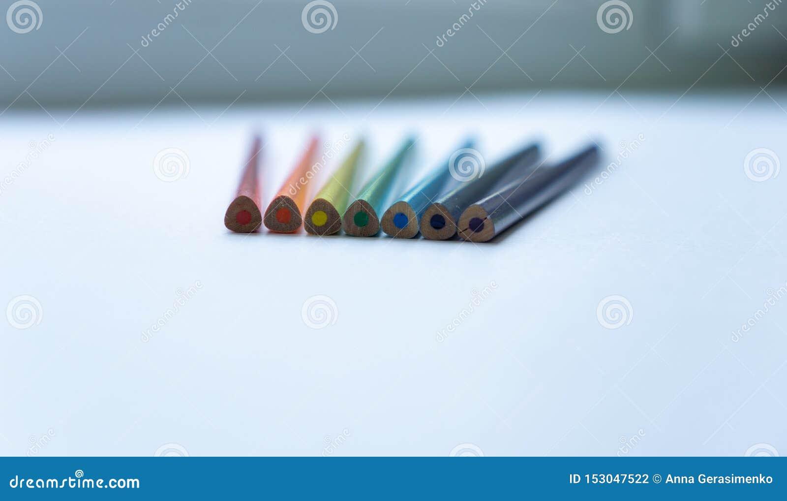 Σύνολο επτά μην ακονισμένων τόξο-χρωματισμένων μολυβιών σε ένα άσπρο υπόβαθρο r