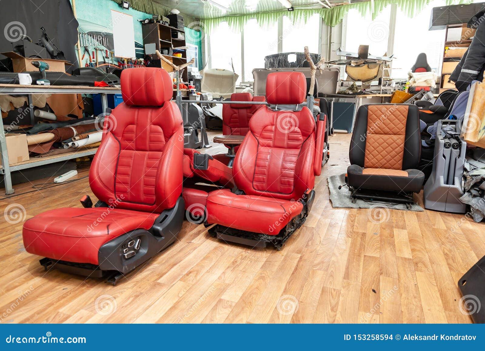 Τέσσερα αθλητικά καθίσματα με το κόκκινο δέρμα τακτοποιούν, τοποθετημένος στο πάτωμα στο εργαστήριο για την επισκευή και το συντο