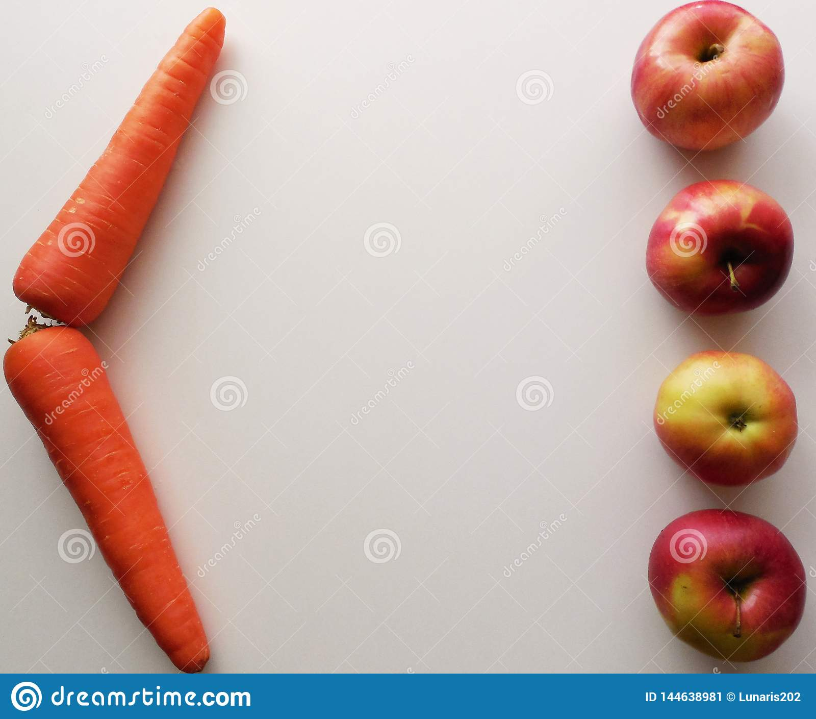 Τέσσερα μήλα και δύο καρότα σε ένα άσπρο υπόβαθρο