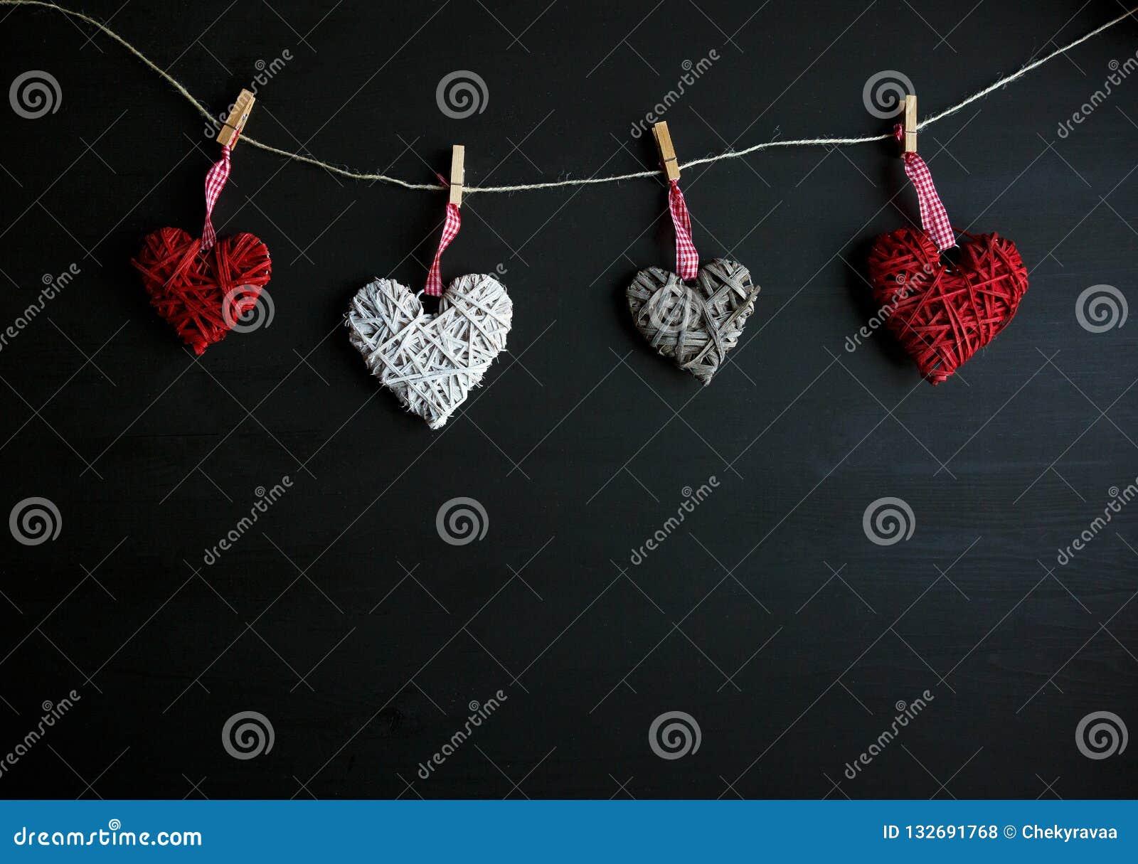 Τέσσερις άσπρες και κόκκινες καρδιές στο μαύρο ξύλινο πίνακα Βαλεντίνοι, υπόβαθρο άνοιξη Χλεύη επάνω με το copyspace ευτυχείς μητ