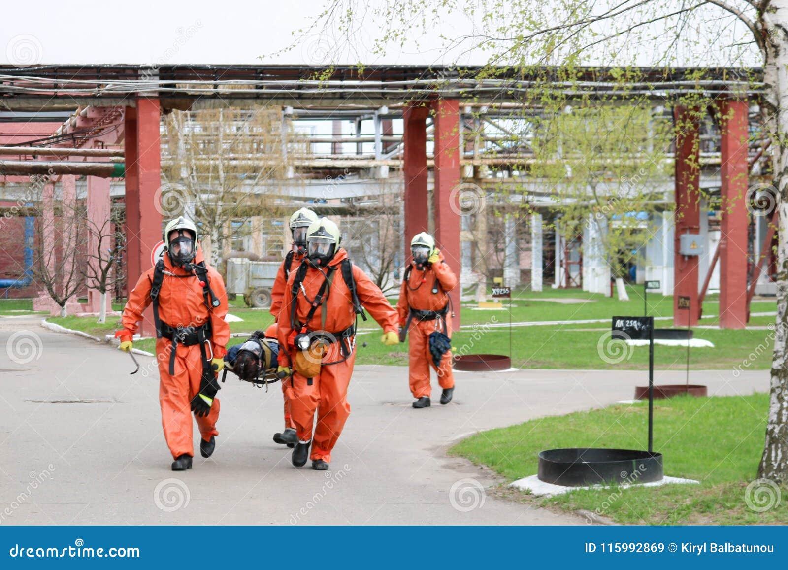 Τέσσερις επαγγελματικοί πυροσβέστες πυροσβεστών στα πορτοκαλιά προστατευτικά αλεξίπυρα κοστούμια, τα άσπρες κράνη και τις μάσκες